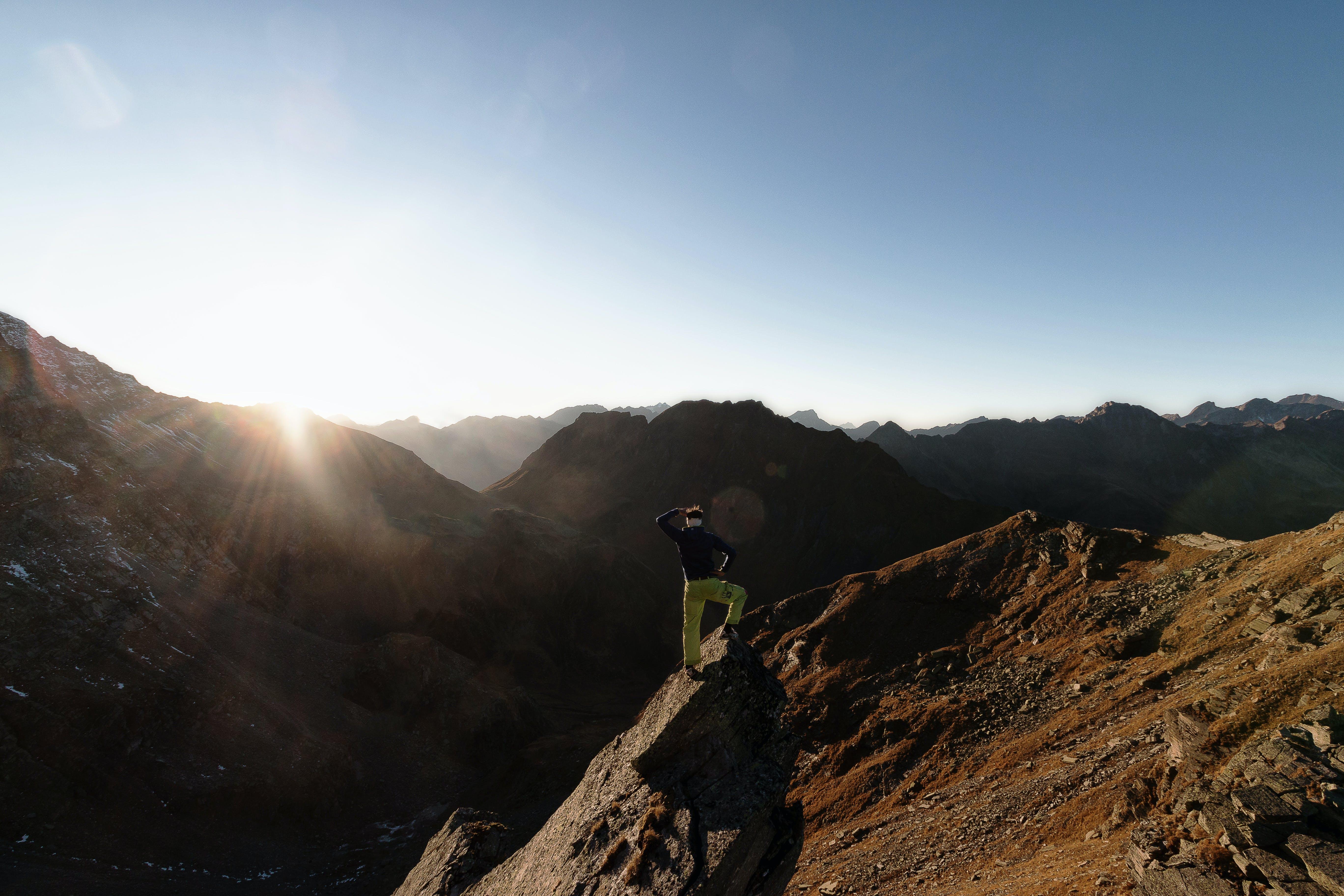 Man Standing on Rock on Top of Mountain Facing Sun