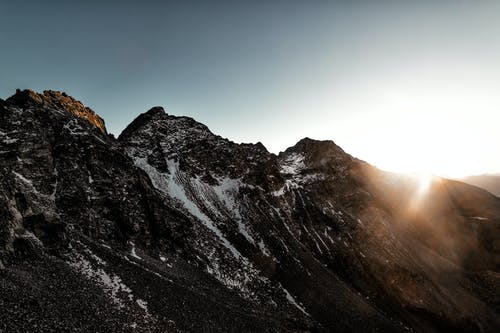 Gray Rock Mountain With White Snow during Sun Rise Aerial Photography