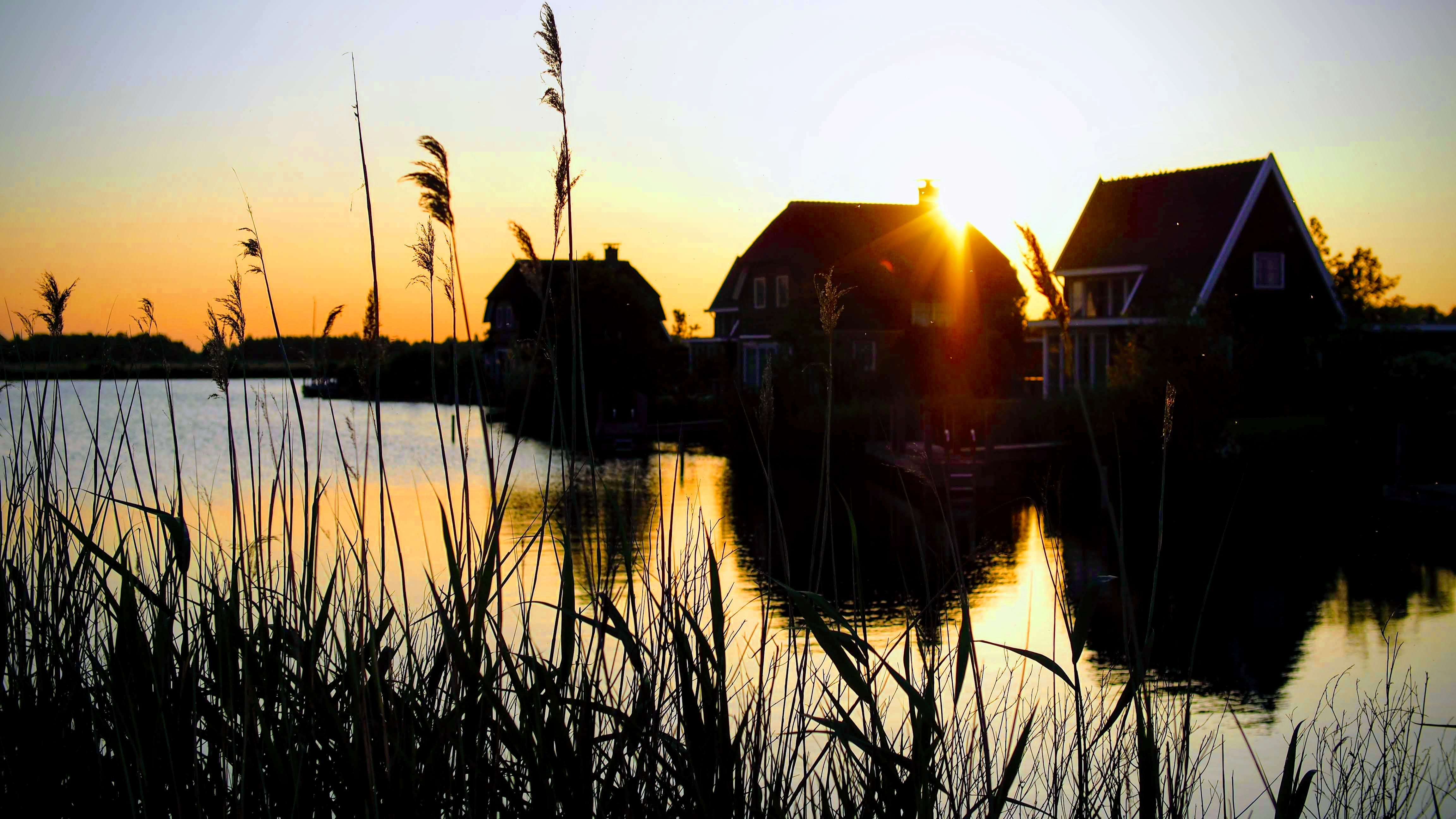 Silhouette Photograph of Houses Beside River