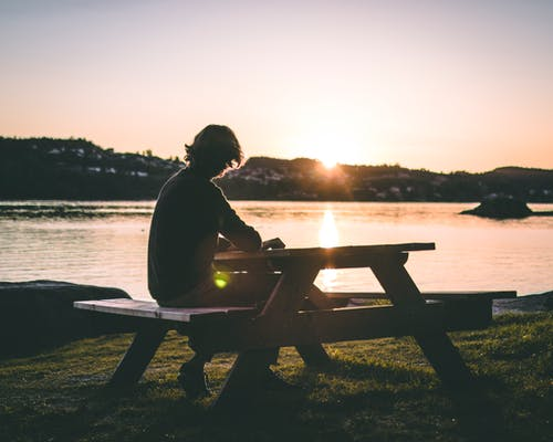 Silhouette of Person in Black Top Sitting on Picnic Bench Near Body of Water during Sunset