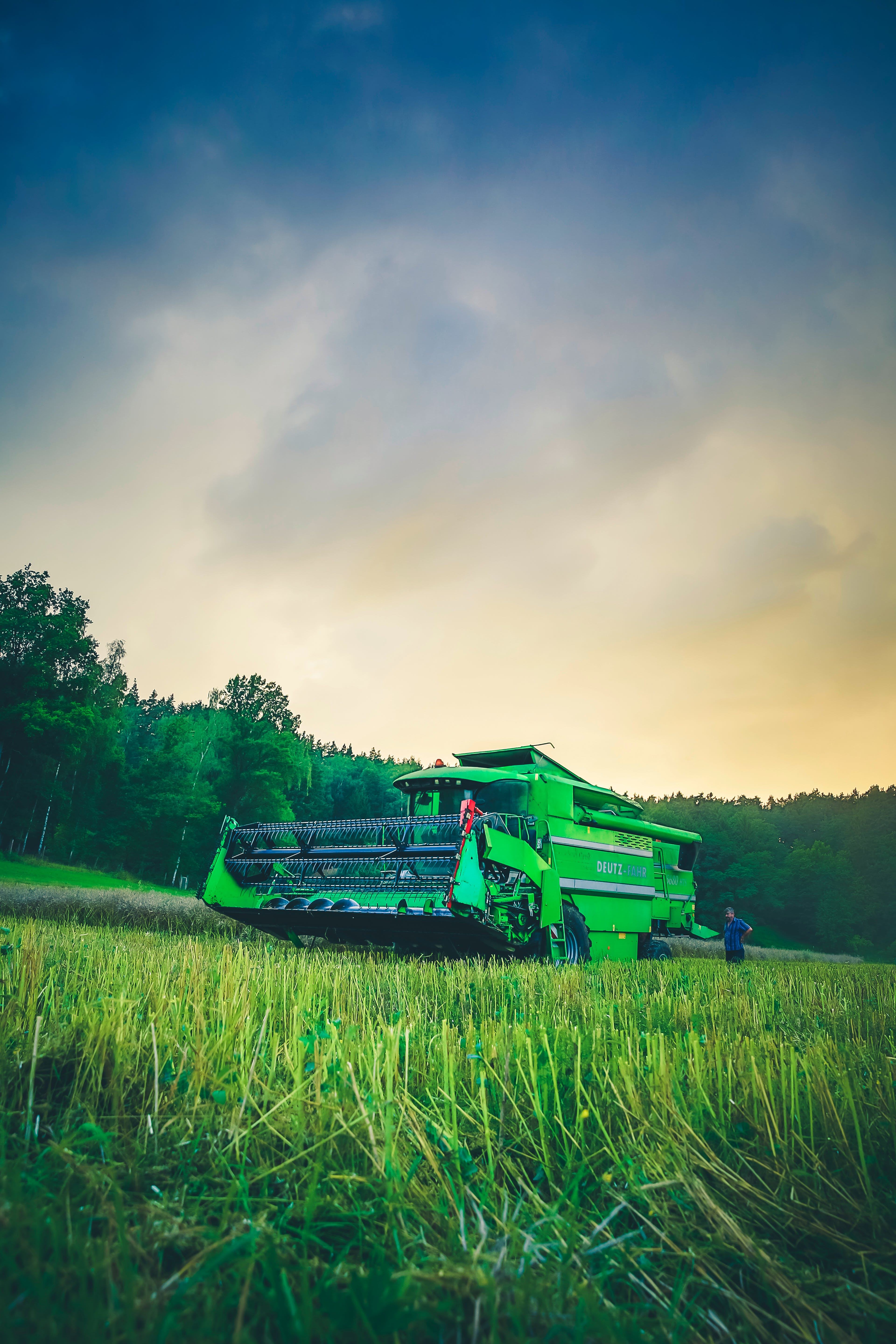 Green Harvester on Green Rice Field Under Blue and White Sky during Daytime