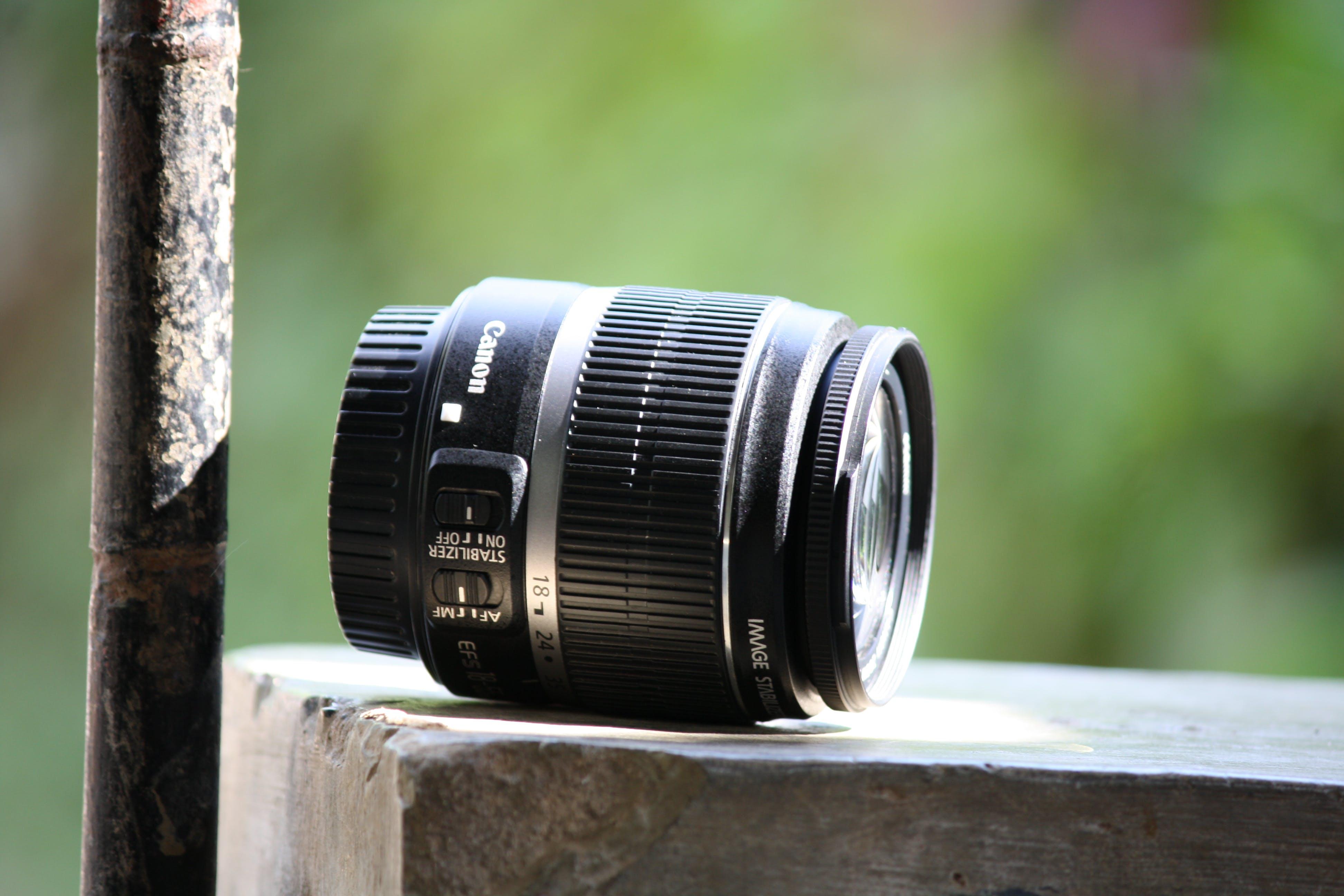 Black Canon Lens on Gray Concrete Table