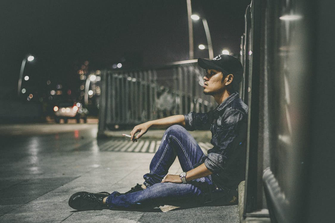 Shallow Focus Photography of Man Sitting Beside Railing Holding Cigarette Stick