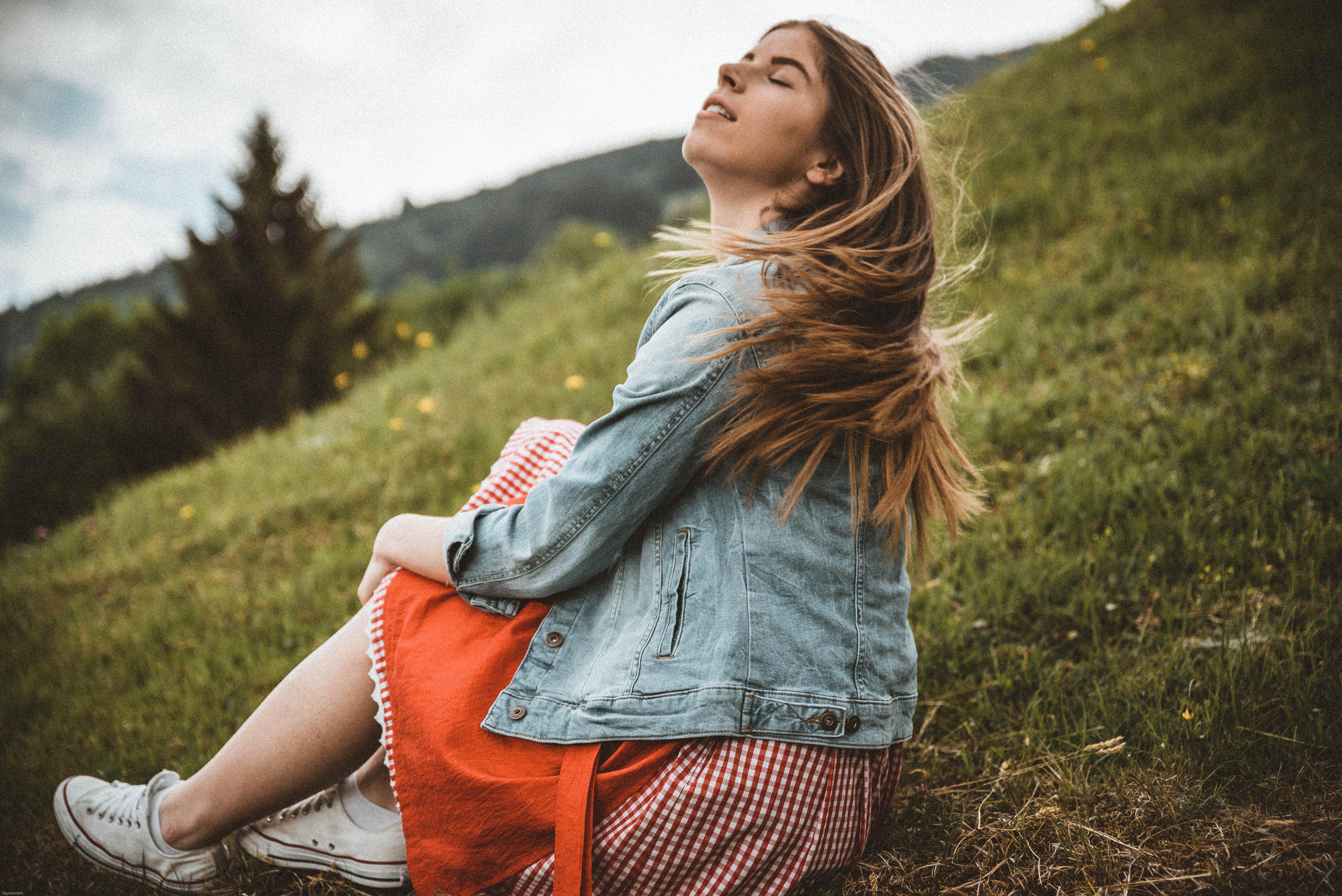 Woman Wearing Blue Denim Jacket Sitting on Green Grass Near Trees Under Blue Sky at Daytime