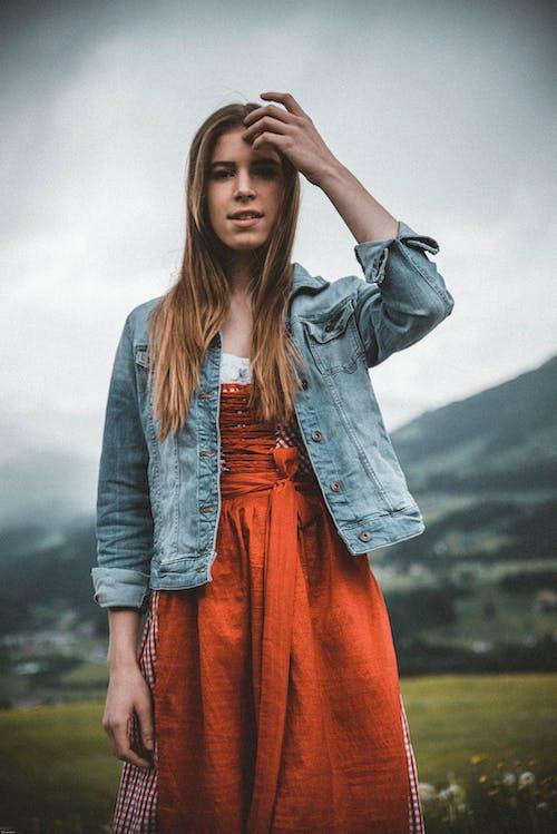 Woman in Blue Denim Button-up Jacket Behind Green Grass Field