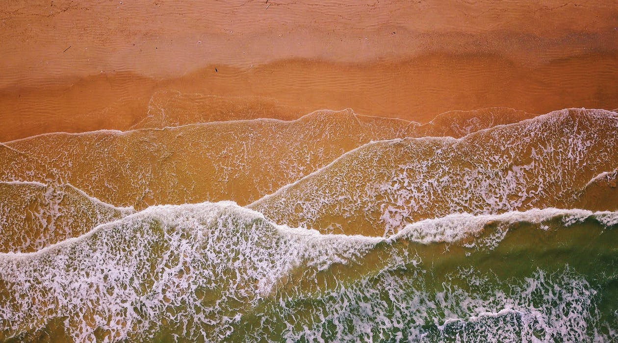 모래 근처의 물 흐름의 항공 사진