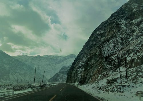 Snow Covered Mountain Ranges Near the Asphalt Road Under the Cloudy Sky