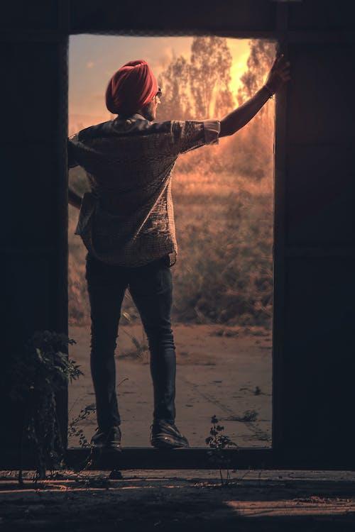 Foto profissional grátis de desgaste, entrada, homem, iluminado por trás