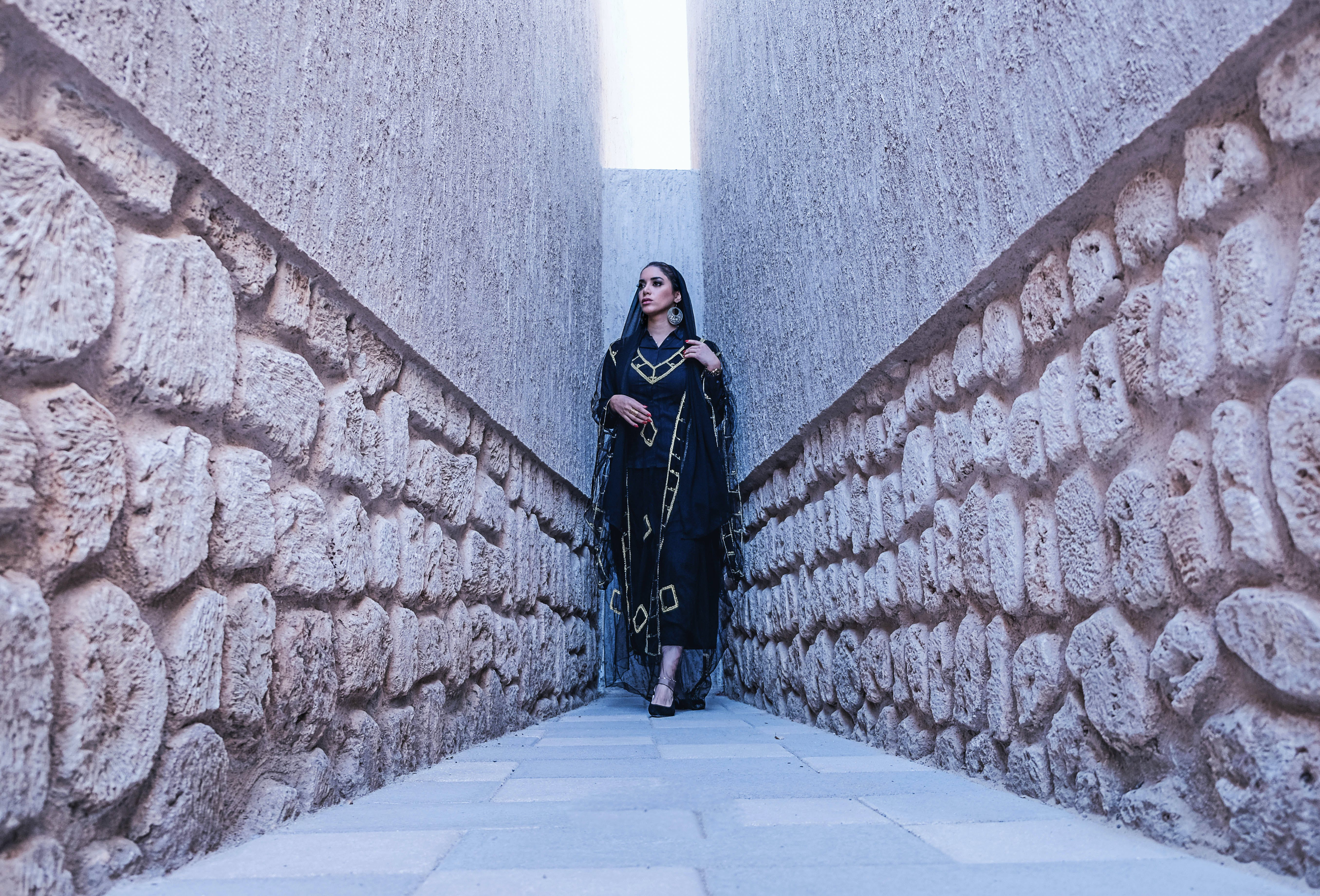 Woman in Black and Gold Traditional Dress Between Gray Concrete Walls