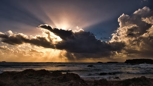Body of Water Under Clouds With Sun Rays