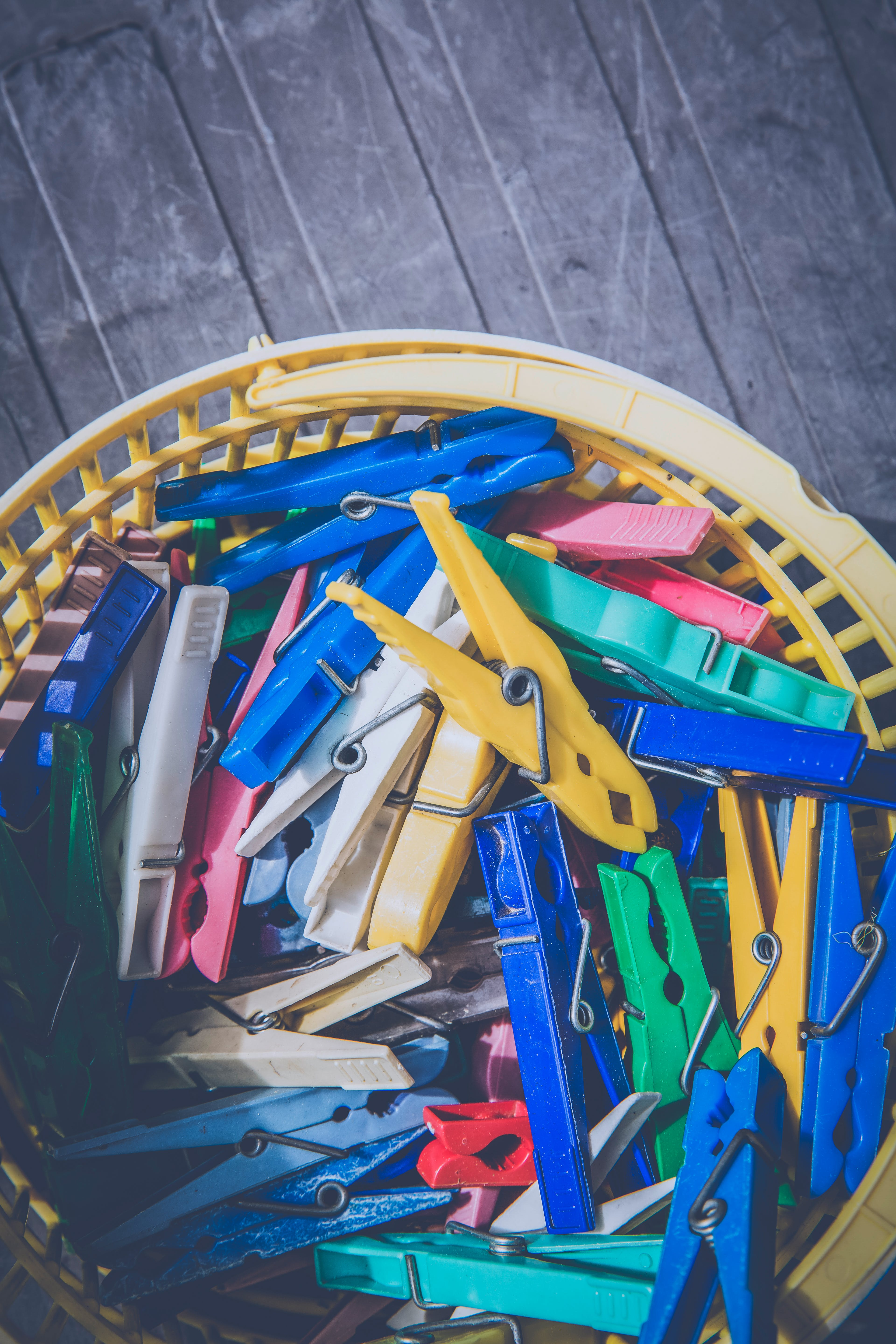 Red Blue Teal Green and Yellow Clothes Pin in Yellow Plastic Bucket