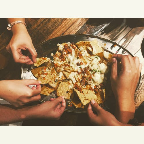 Close-up Photography of People Picking Nachos Chips