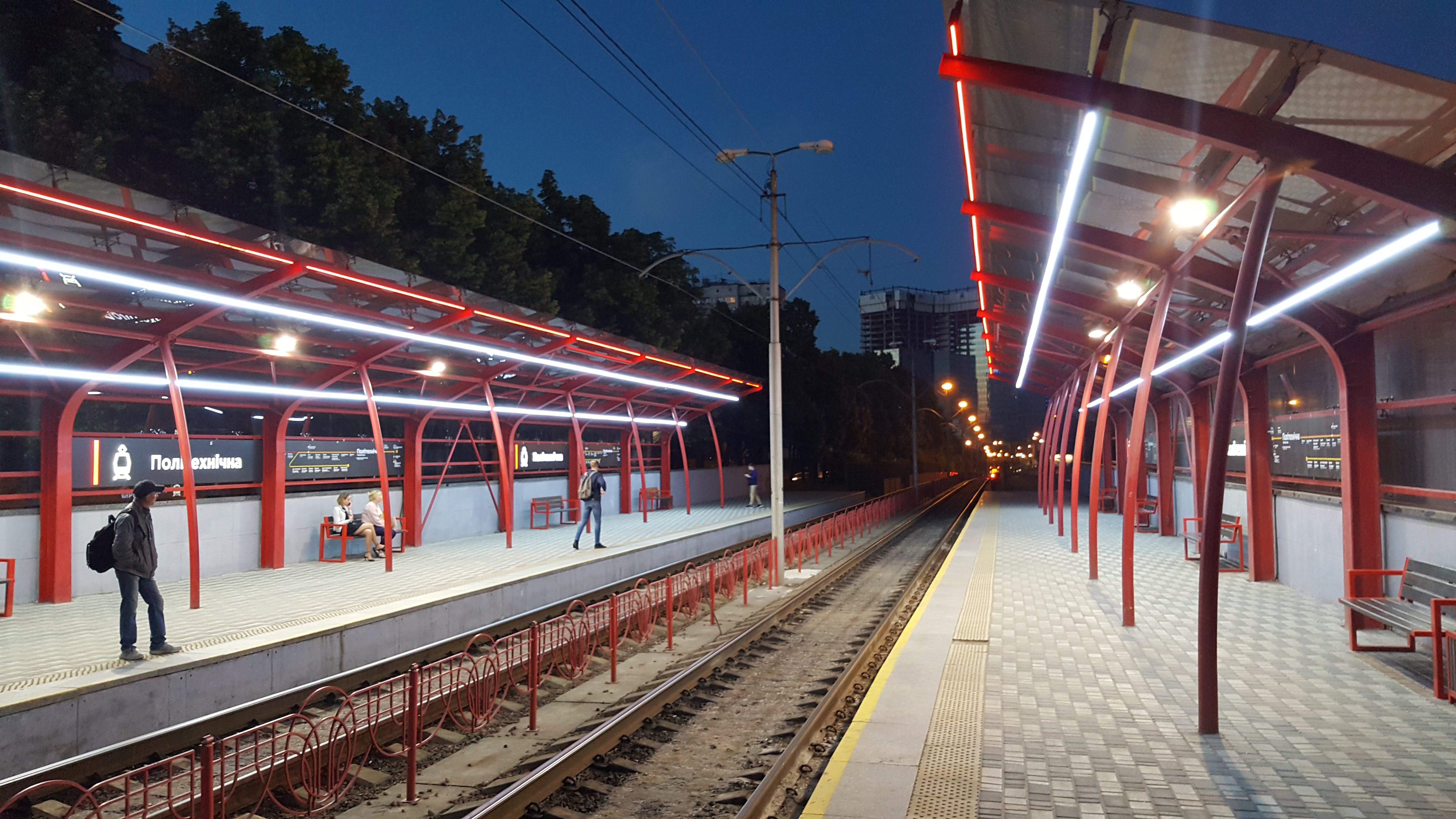 Man Waiting on Train Platform during Nighttime