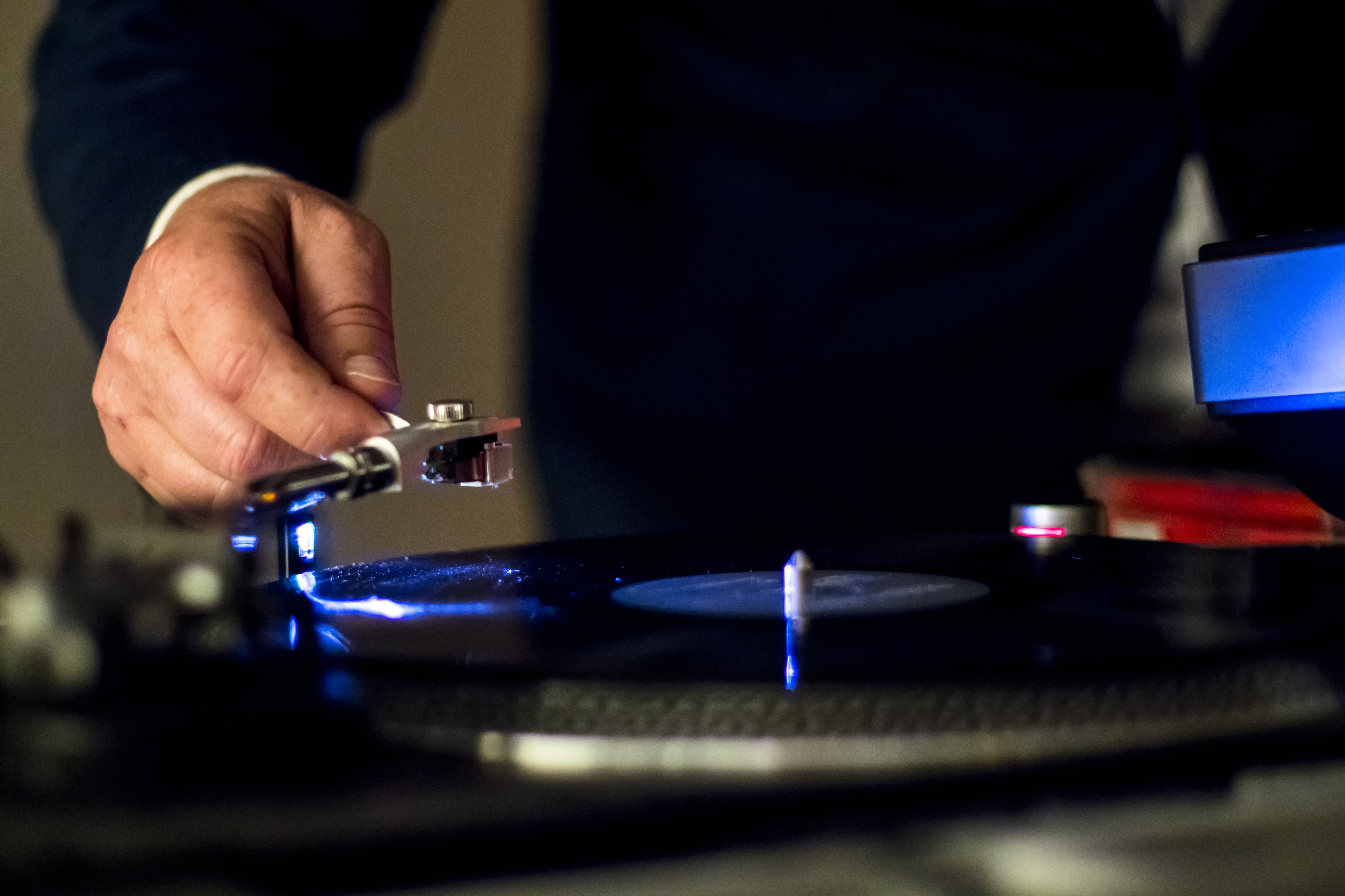 person holding vinyl player in shallow focus photography