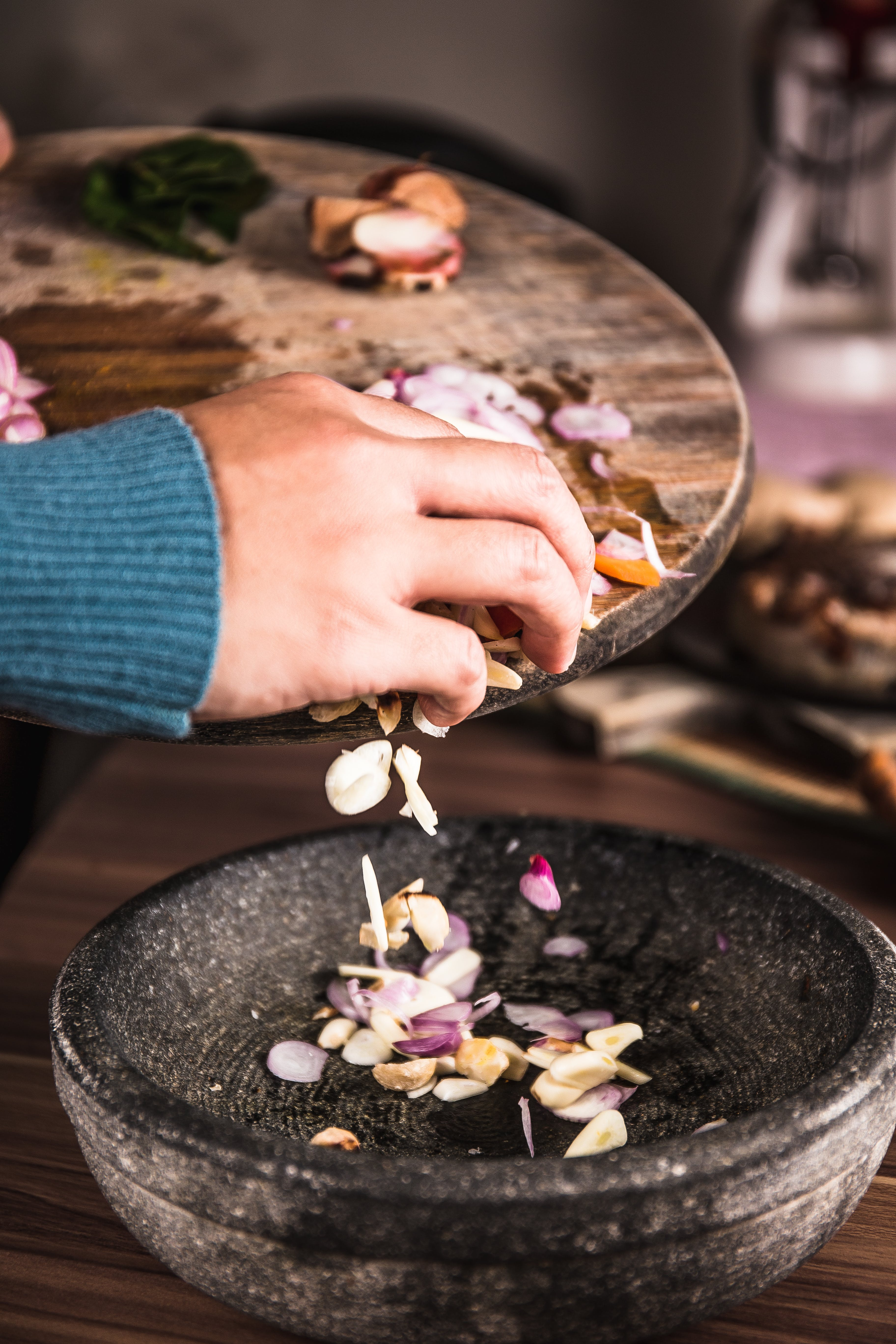 Person Pouring Sliced Spices from a Chopping Board to Black Bowl