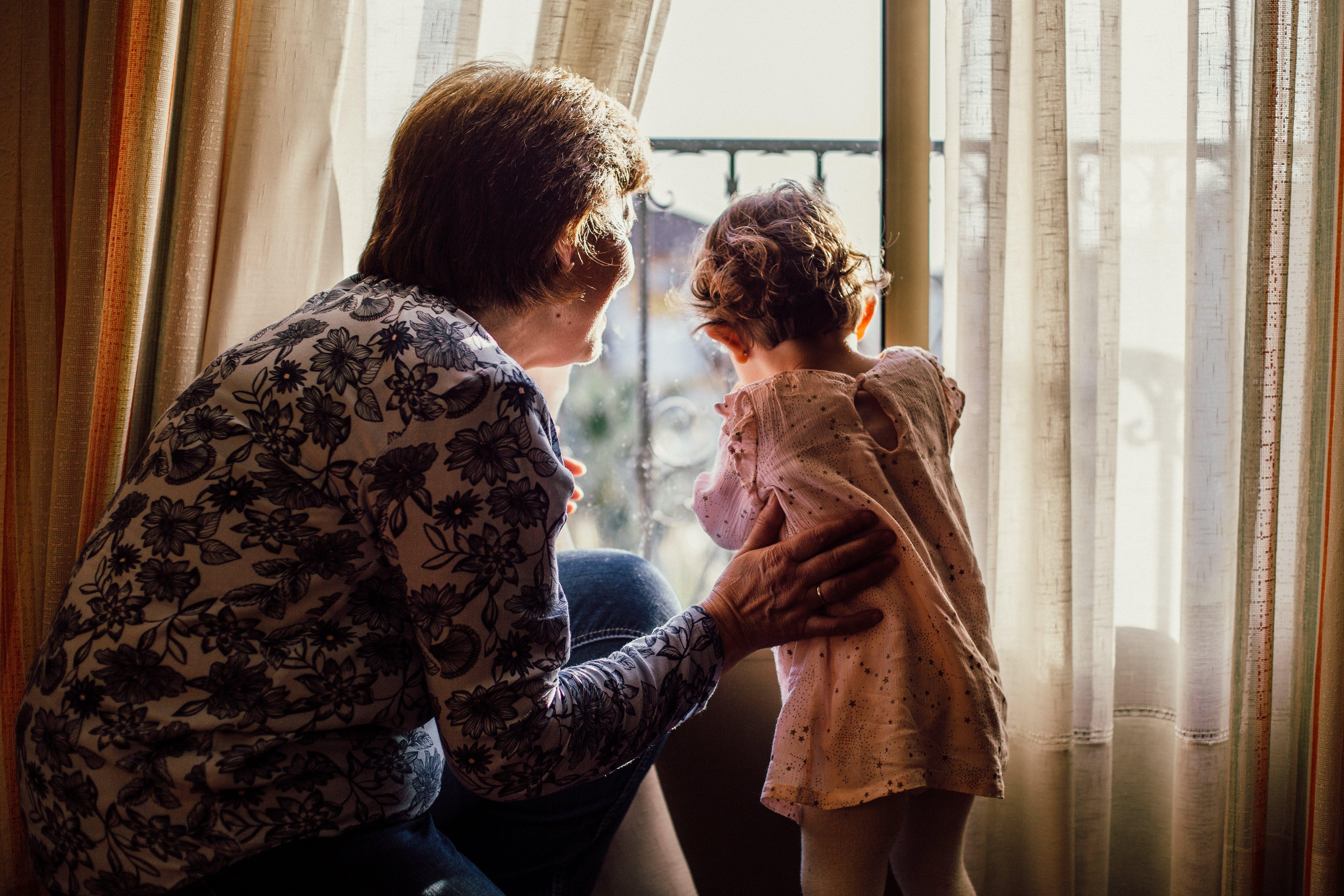 Woman Holding Baby Near Window