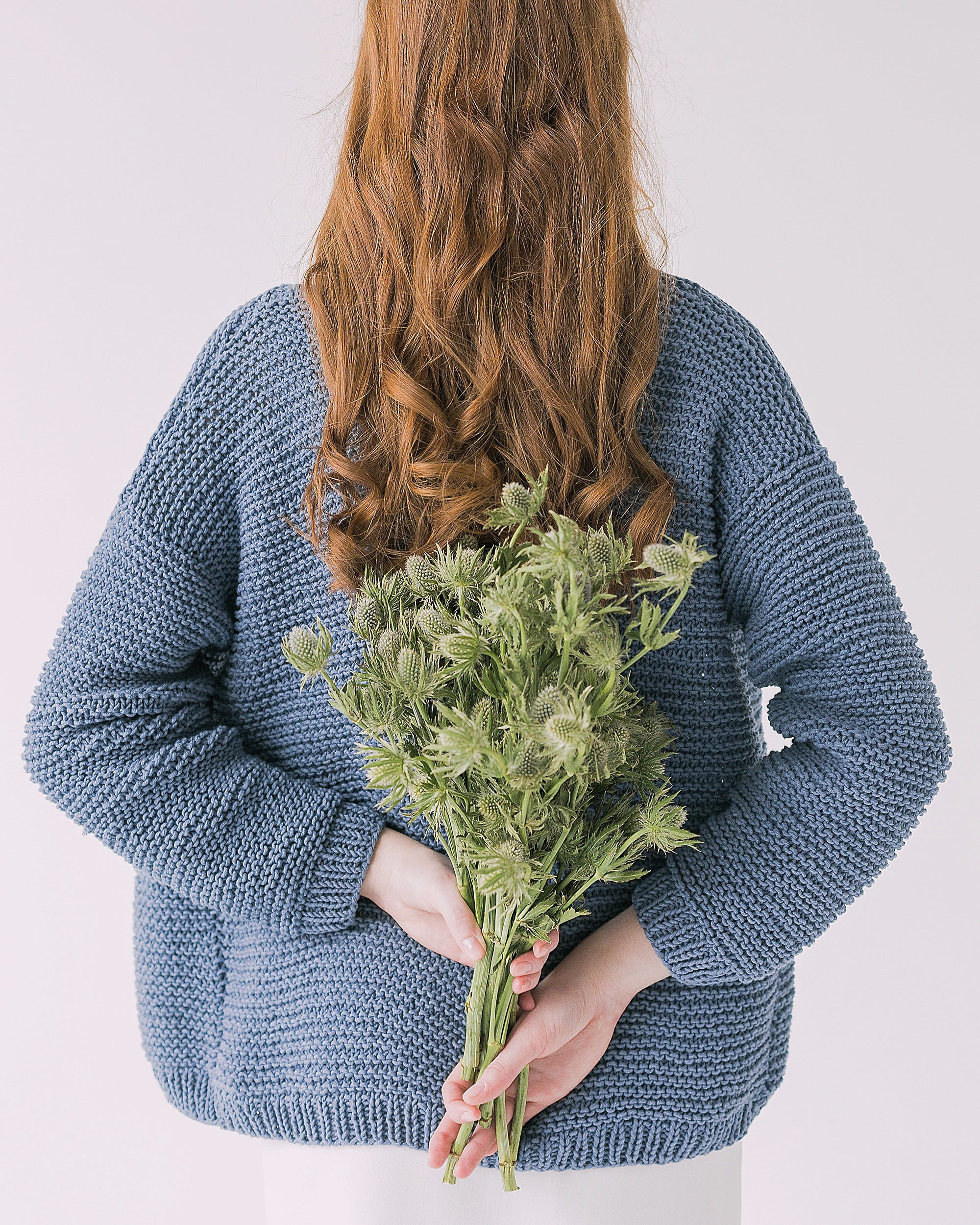 Woman in Gray Sweater Holding Green Leaf Plants
