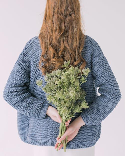 Vrouw In Grijze Trui Met Groene Bladplanten