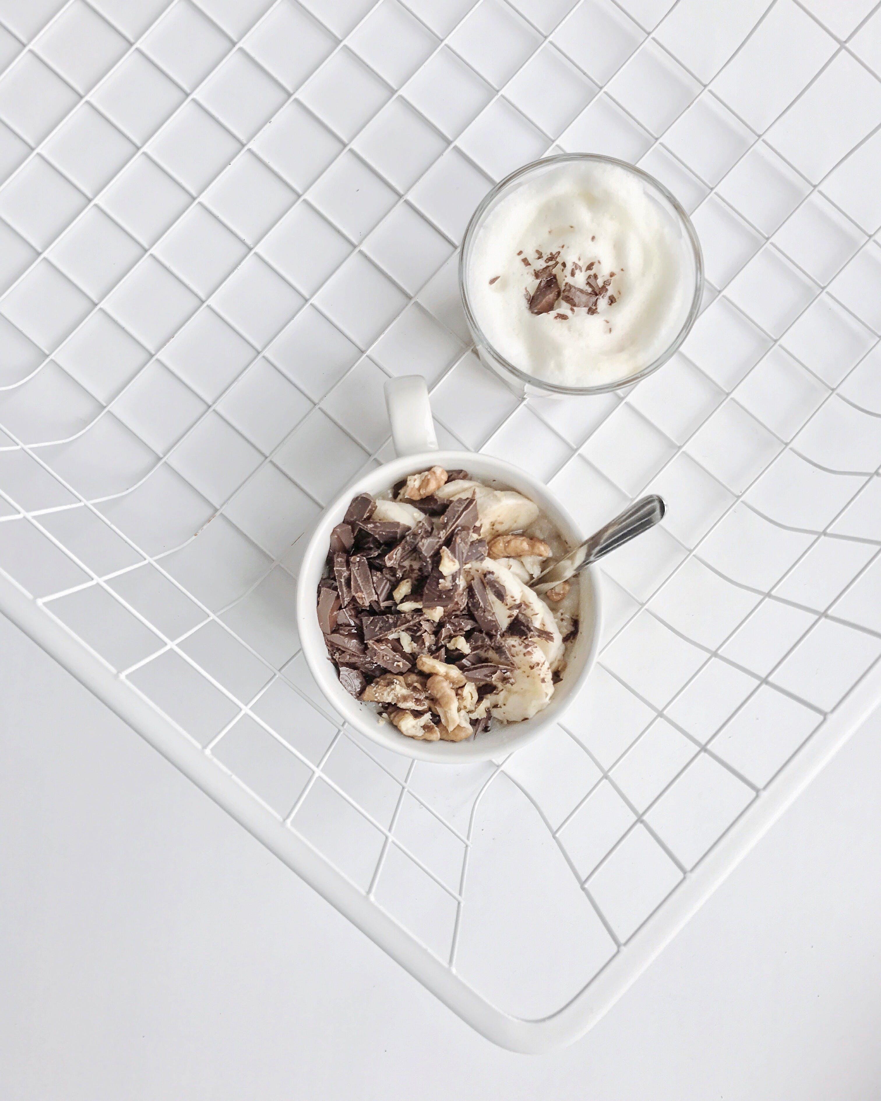 Crushed Nuts and Chocolates on White Ceramic Mug High-angle Photography