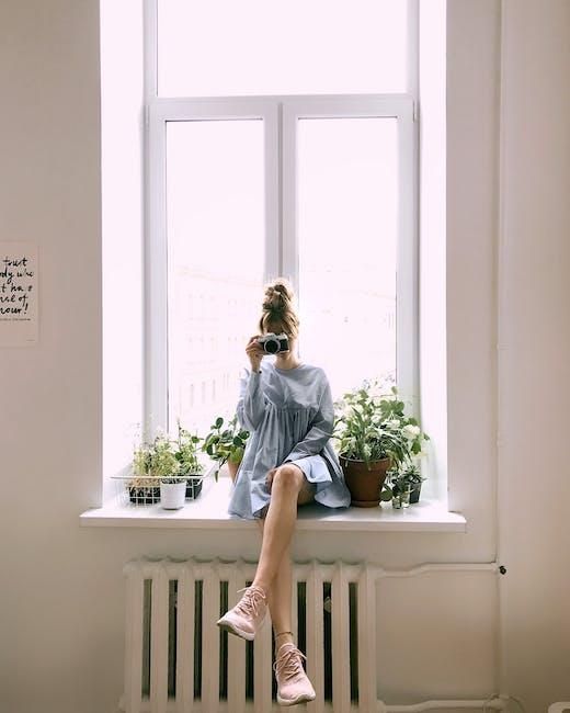 Woman in grey long sleeved dress sitting on window