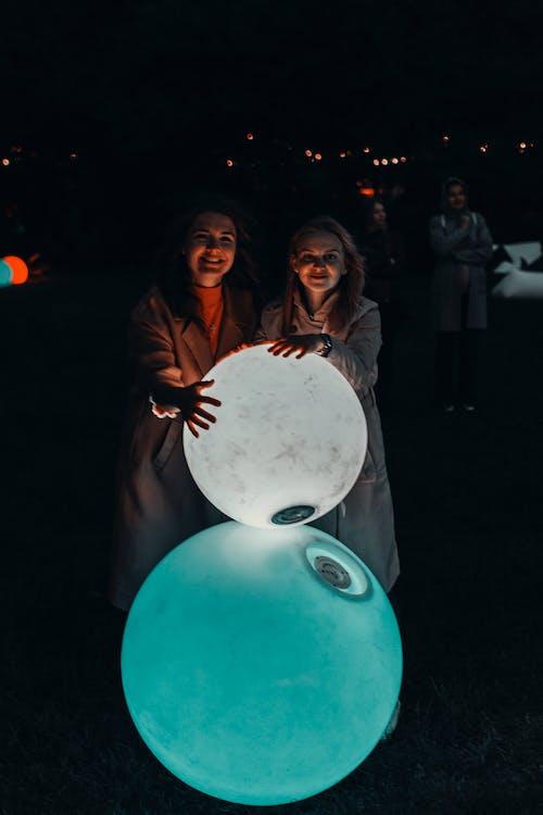 Two Women Holding Lighted Balls