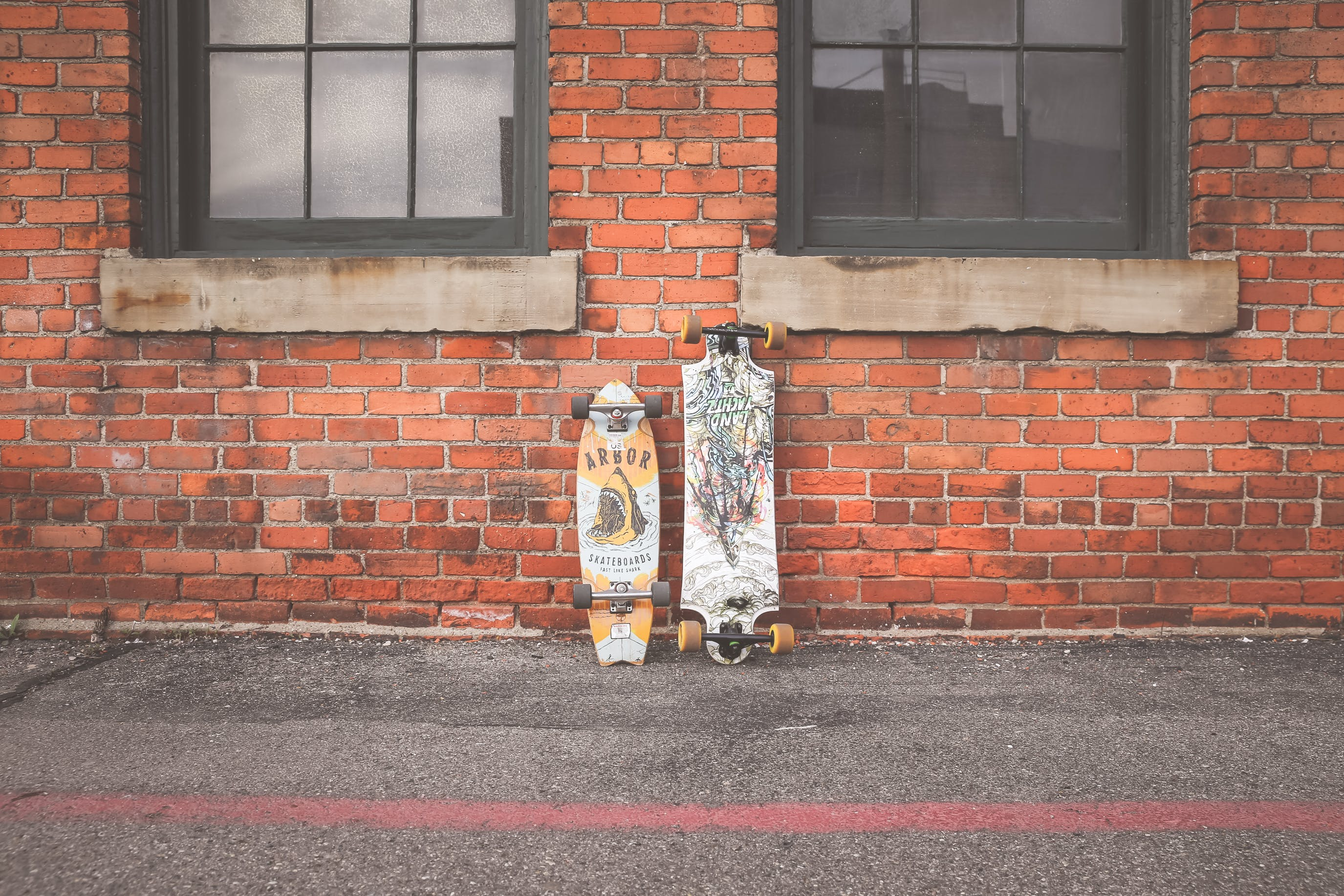Two White and Brown Longboard Leaning on Brown Bricks Wall