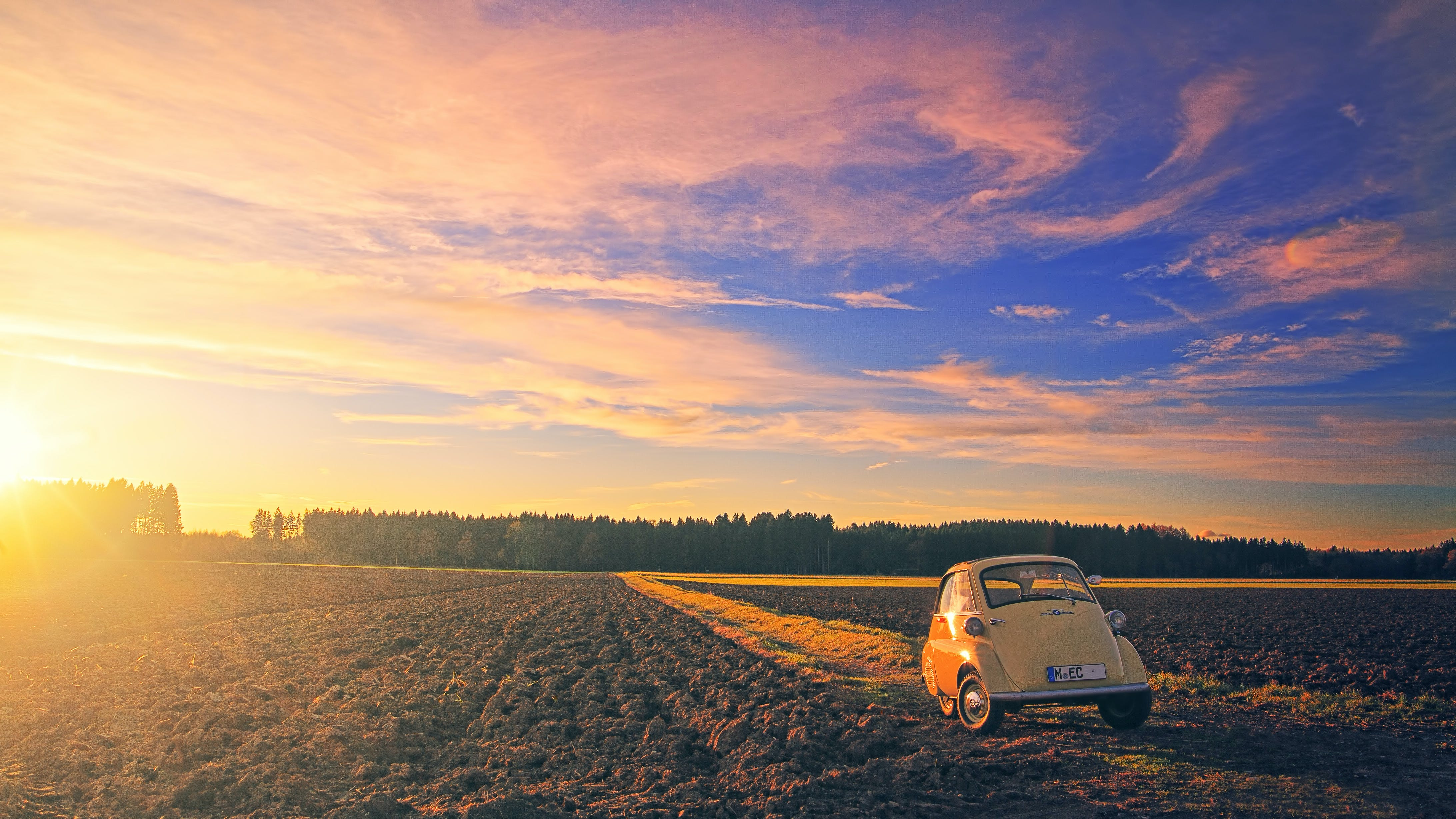 Yellow Classic Car Parked on Field Under Cloudy Sky at Golden Hour