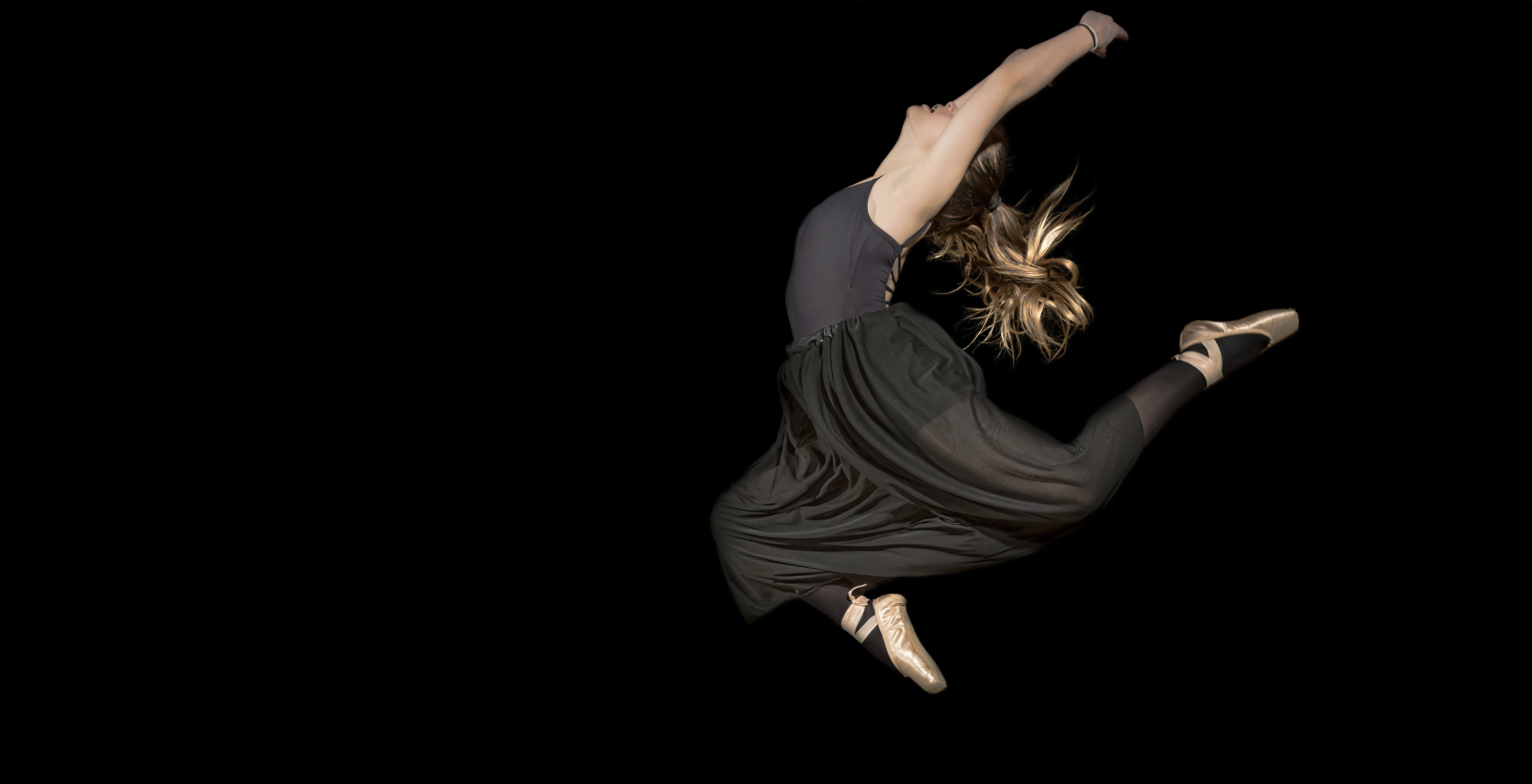 Woman in Black Sleeveless Shirt and Pants Jumping
