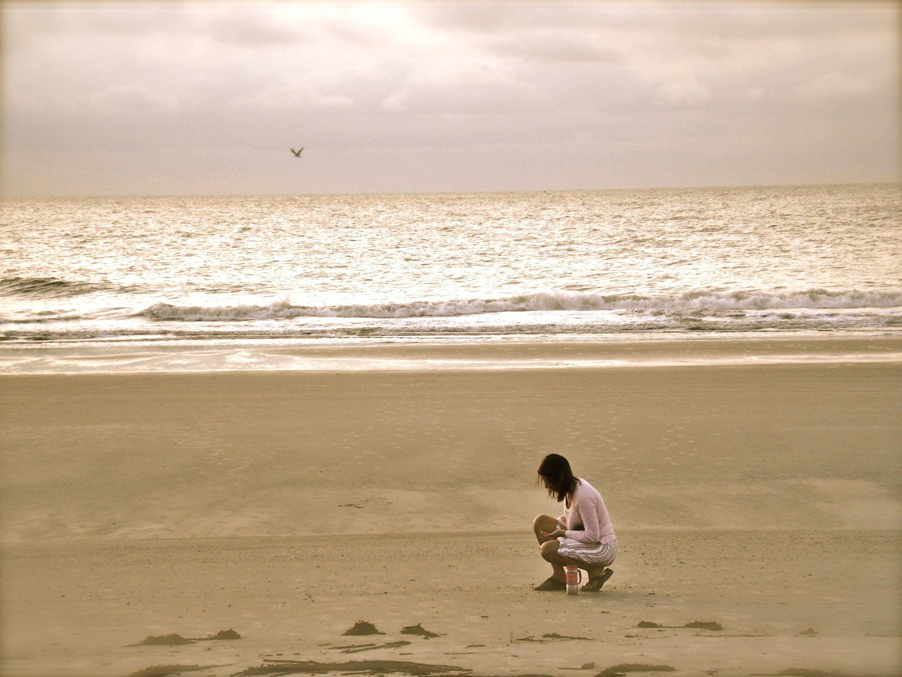 Woman in Pink Cardigan Sitting on Seashore