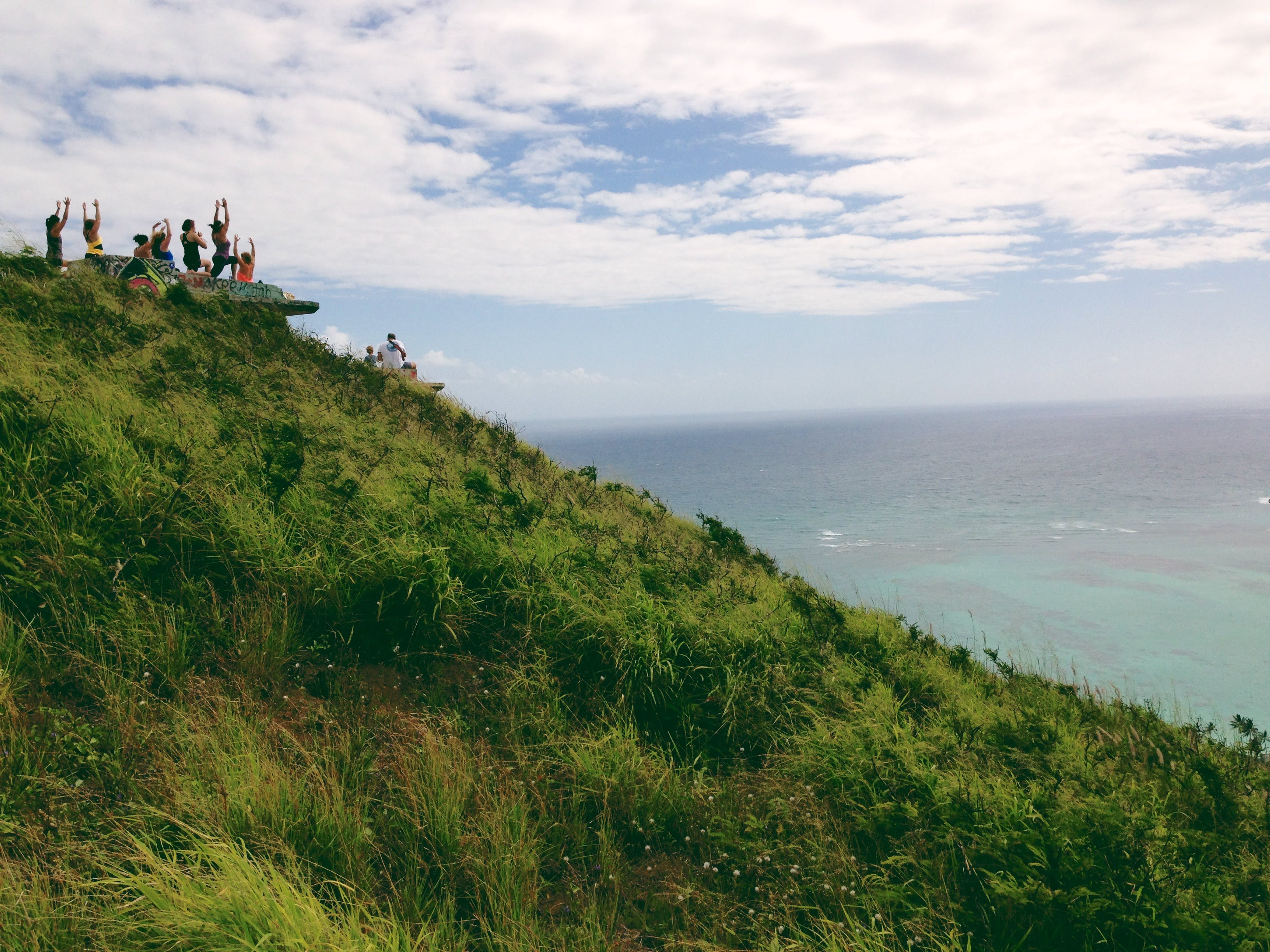 People Standing on a Green Mountain Peak Watching the Clear Blue Body of Water