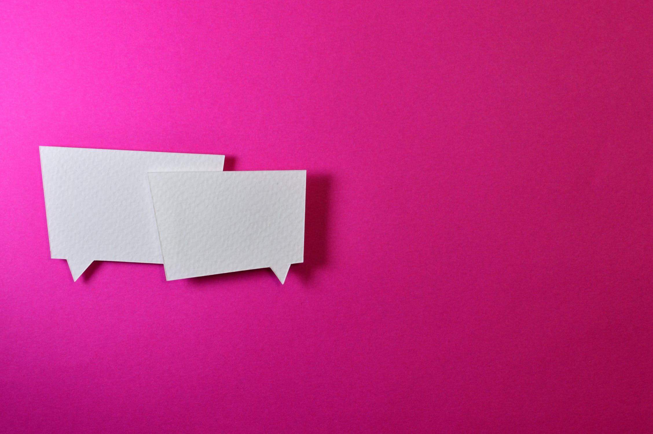 Two speech bubbles on a pink background