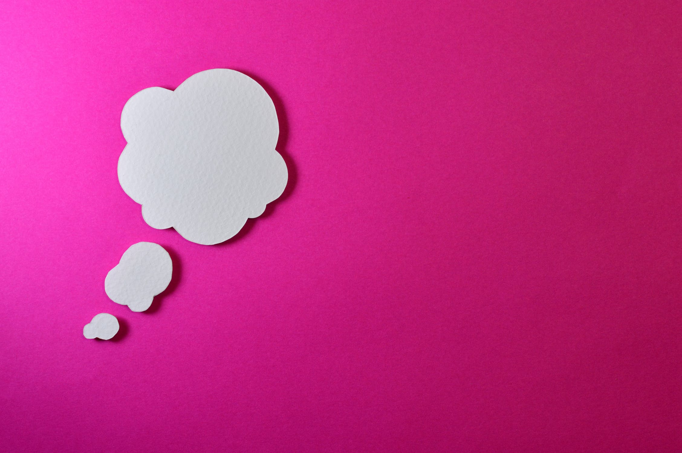A thought bubble floating on a pink background
