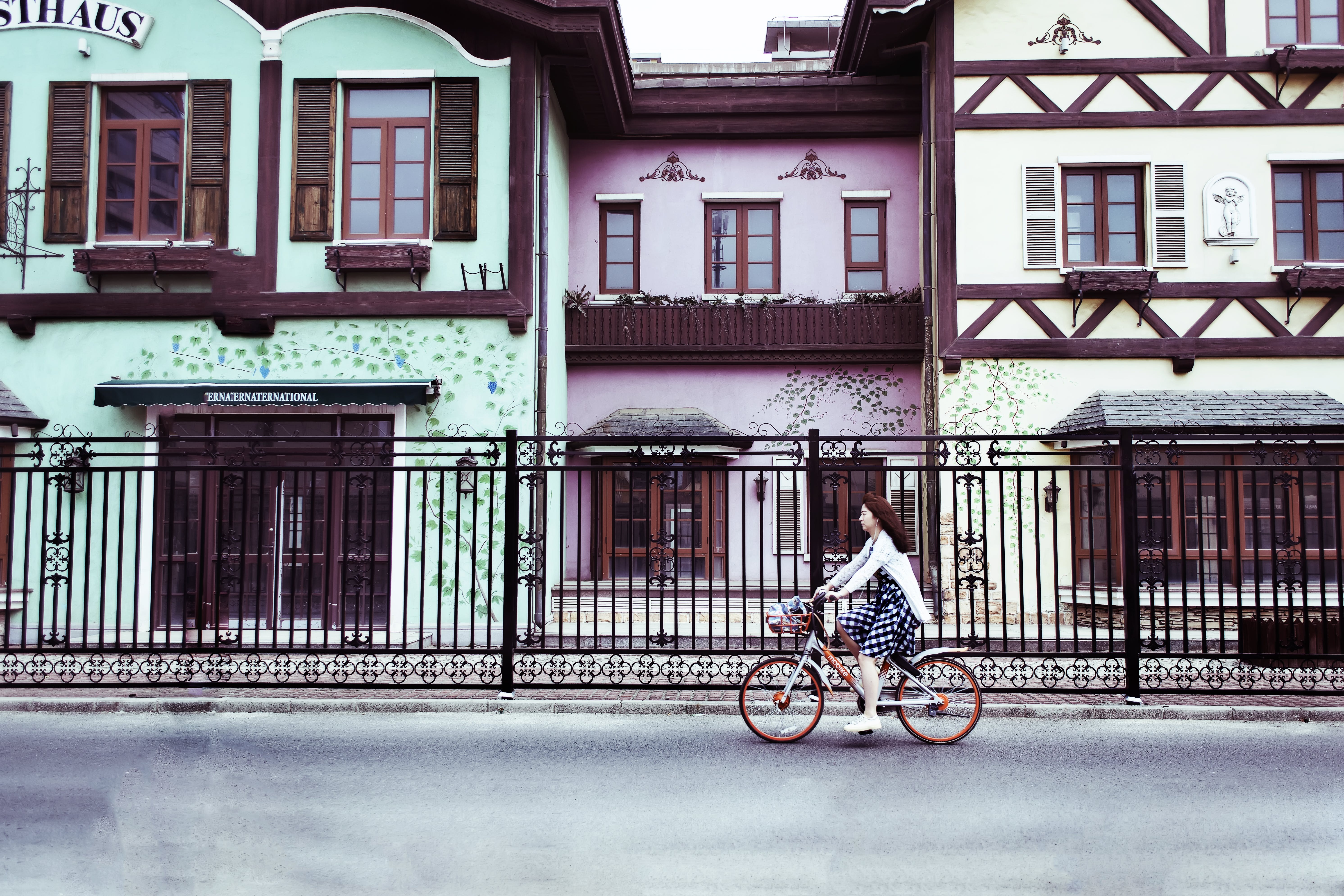 Woman Riding on Bicycle Near Concrete Houses
