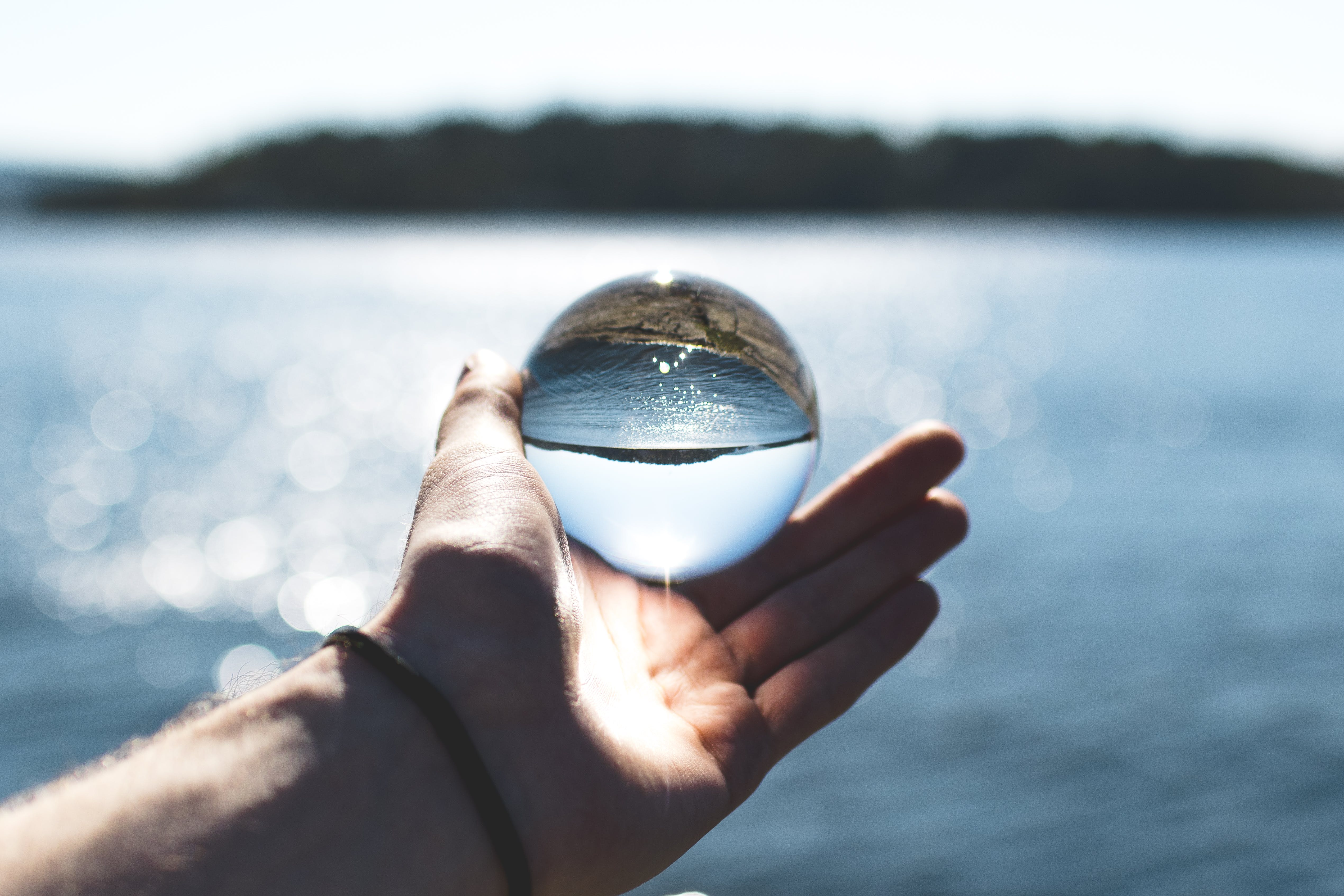 Bokeh Photography of Person Holding Water Drop