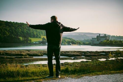 Man Wearing Black Jacket Near on Body of Water