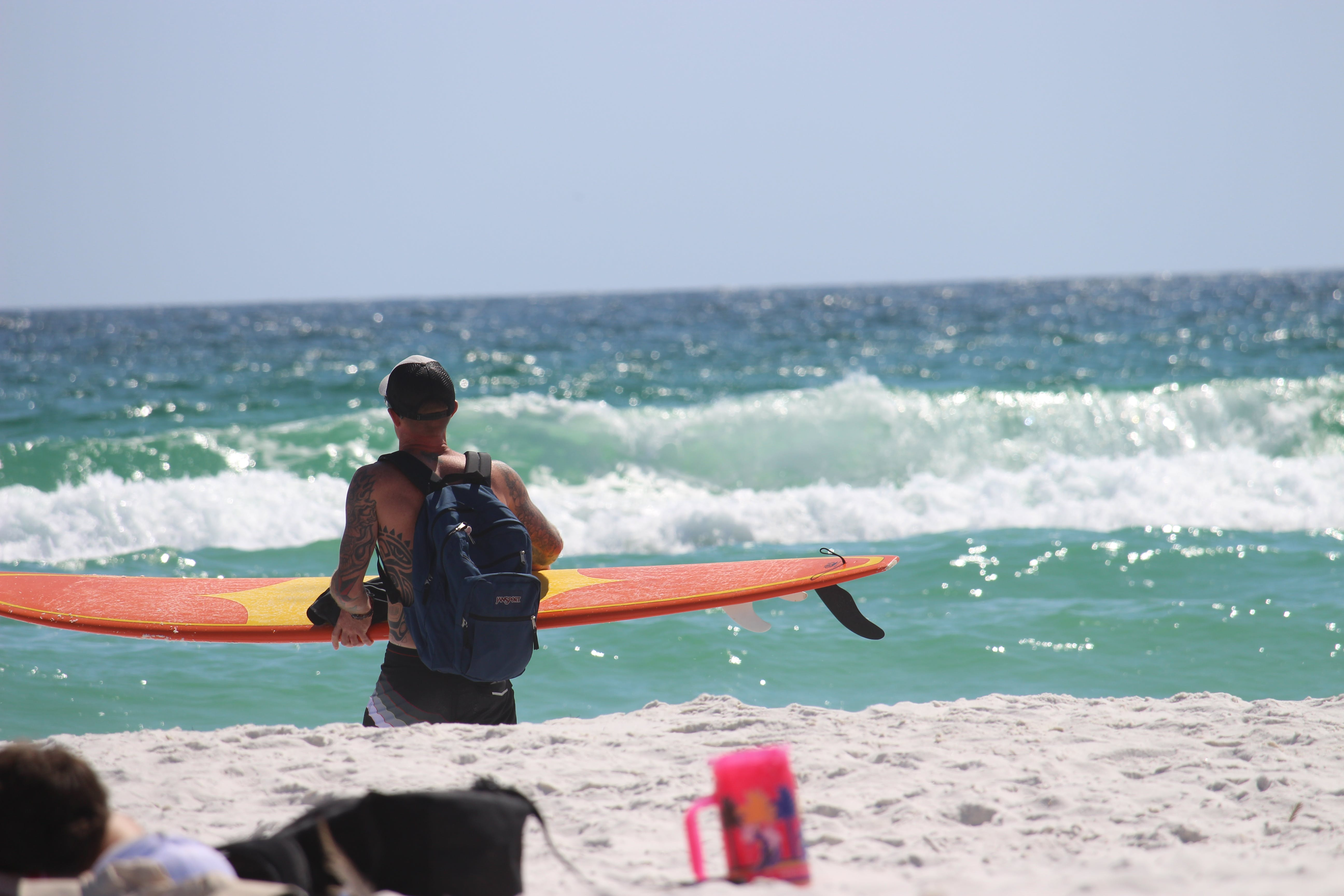 Man Carrying Orange Surfboard on Shore
