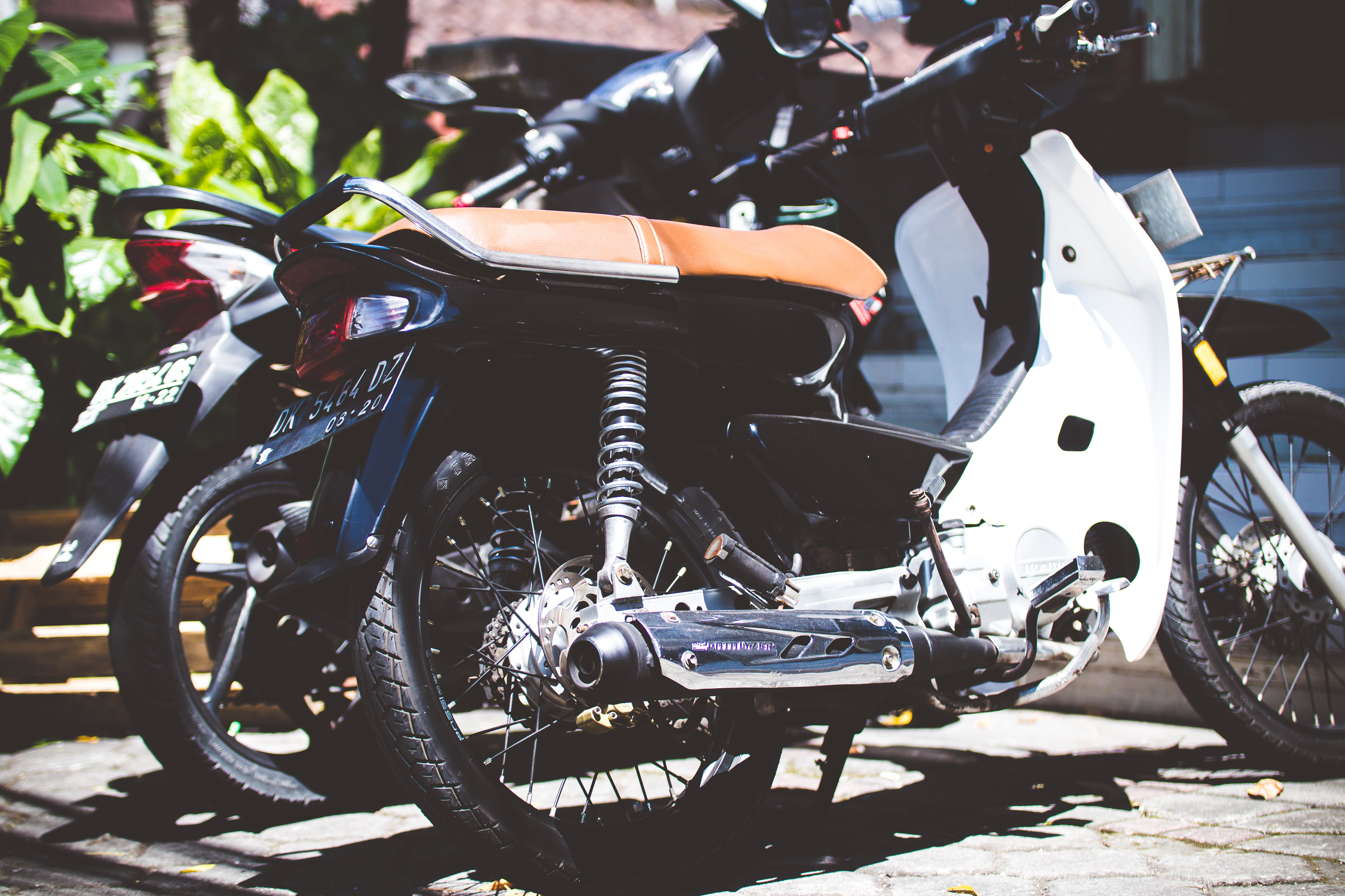 White Underbone Motorcycle Parked Beside a Motorcycle