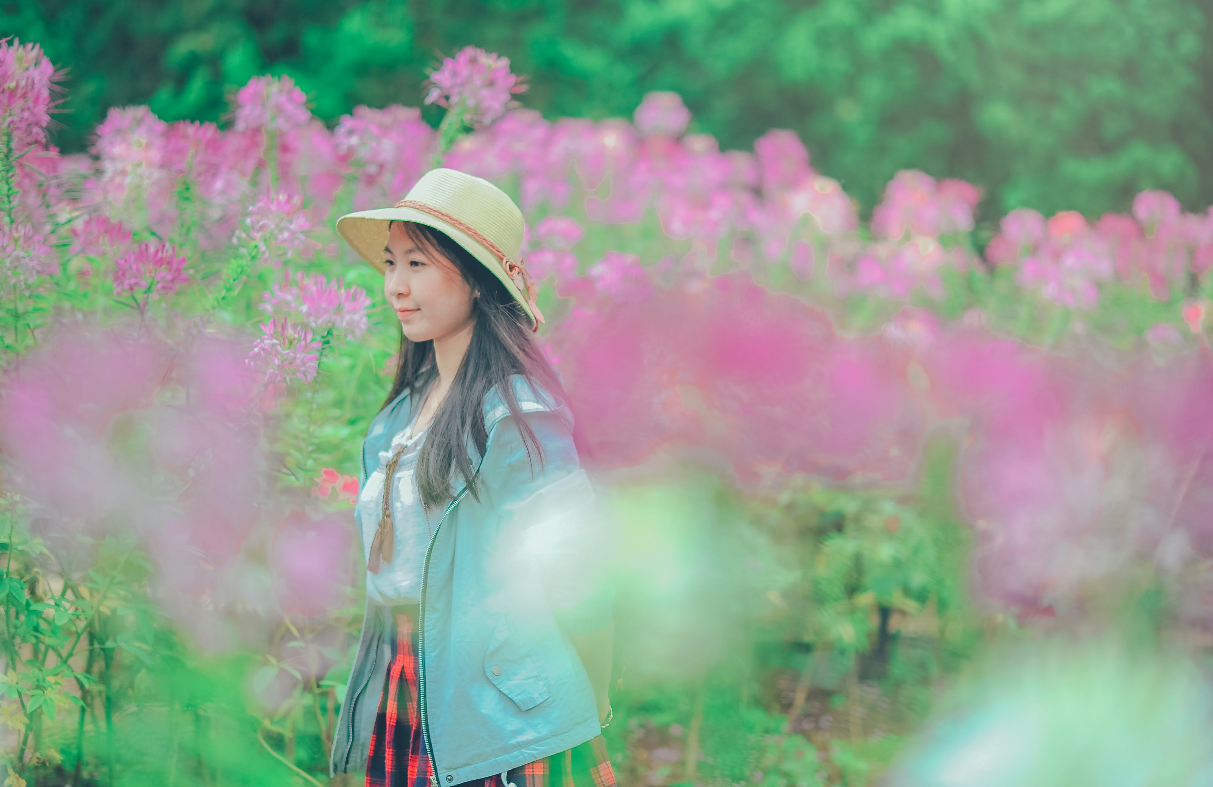 Woman Wearing Sun Hat and Blue Jacket Standing Surrounded by Flowers