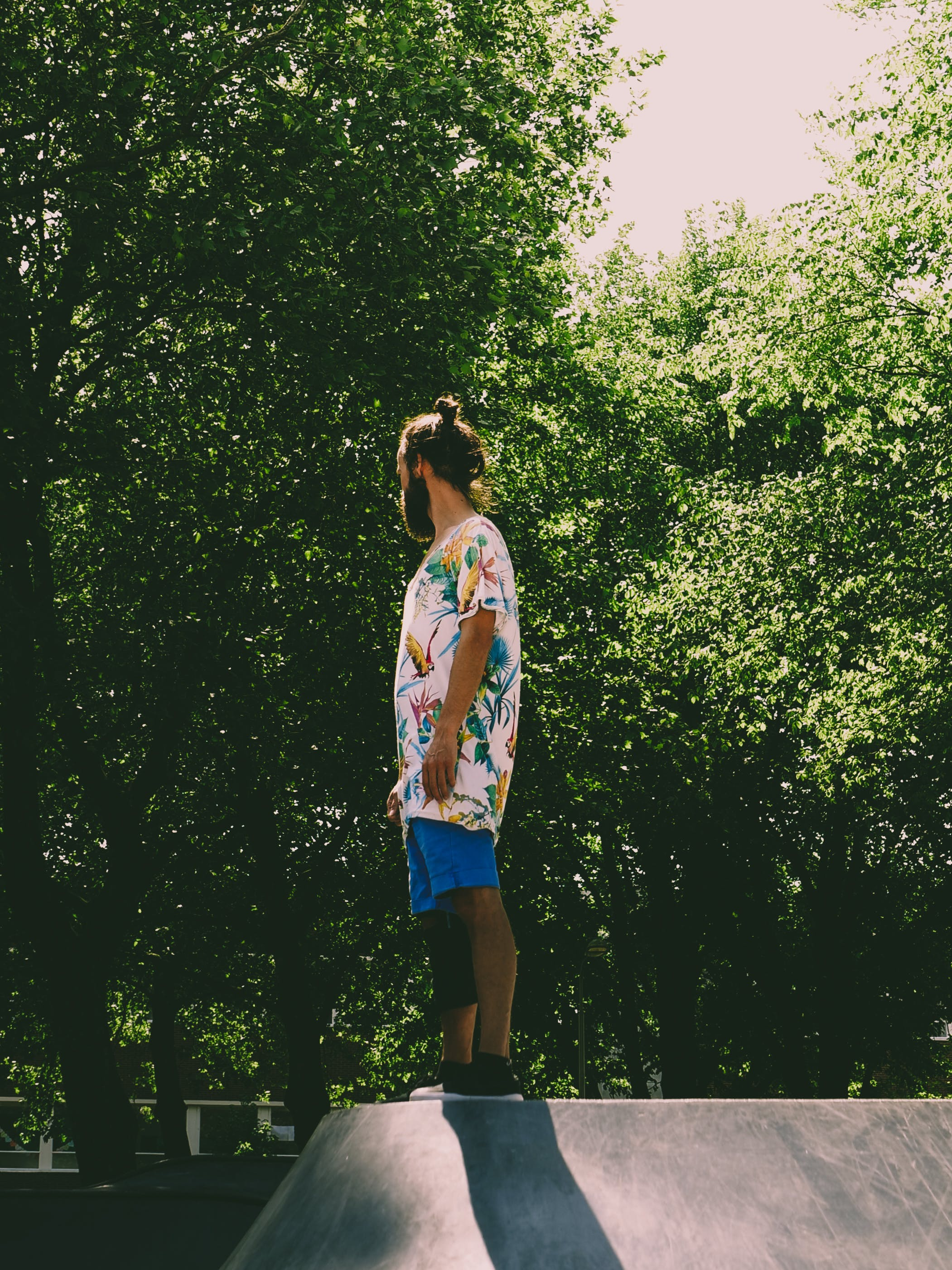 Man Wearing White and Multicolored Floral Standing Near Trees
