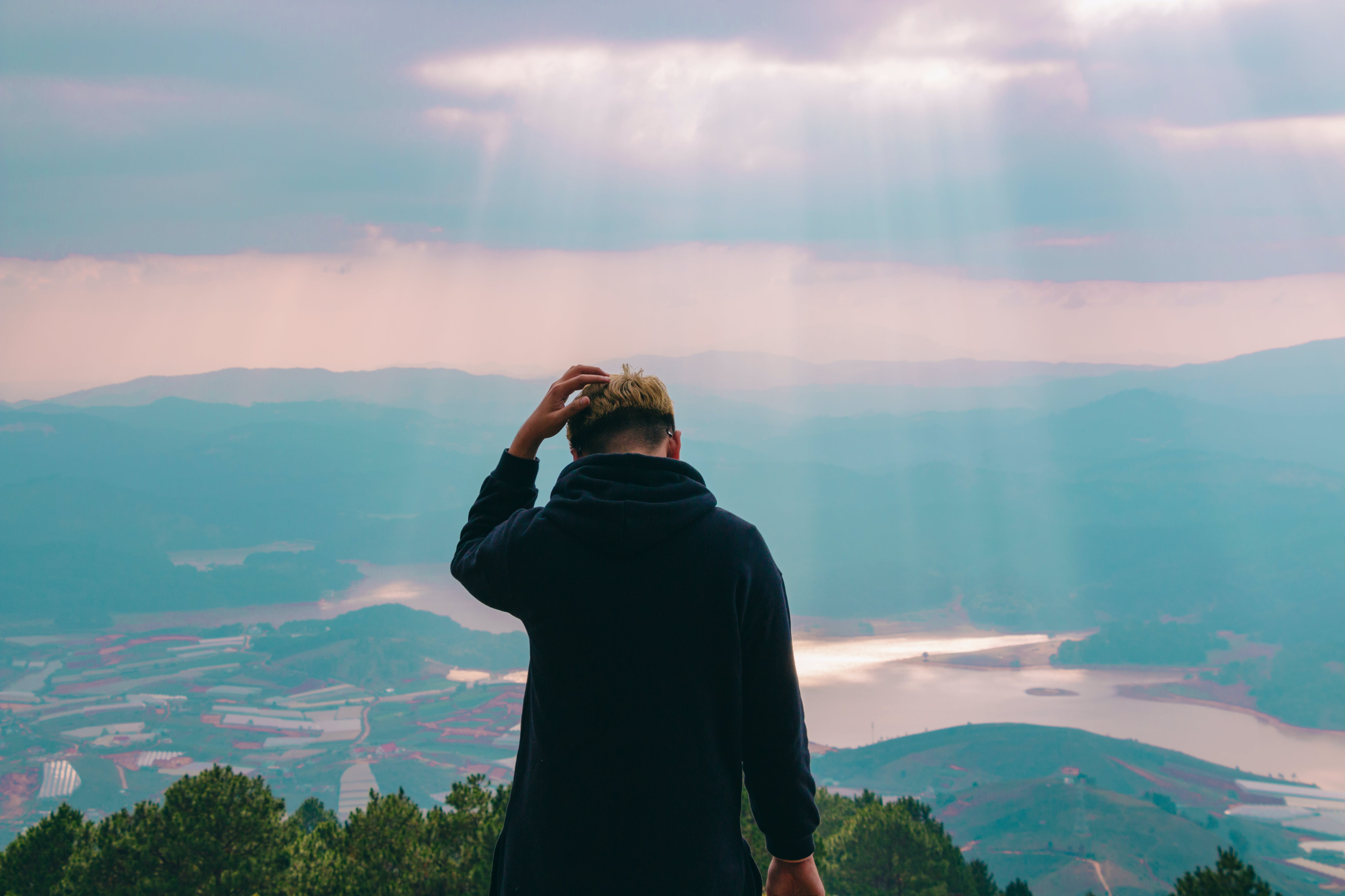 Man in Black Jacket Holding His Hair Facing Body of Water