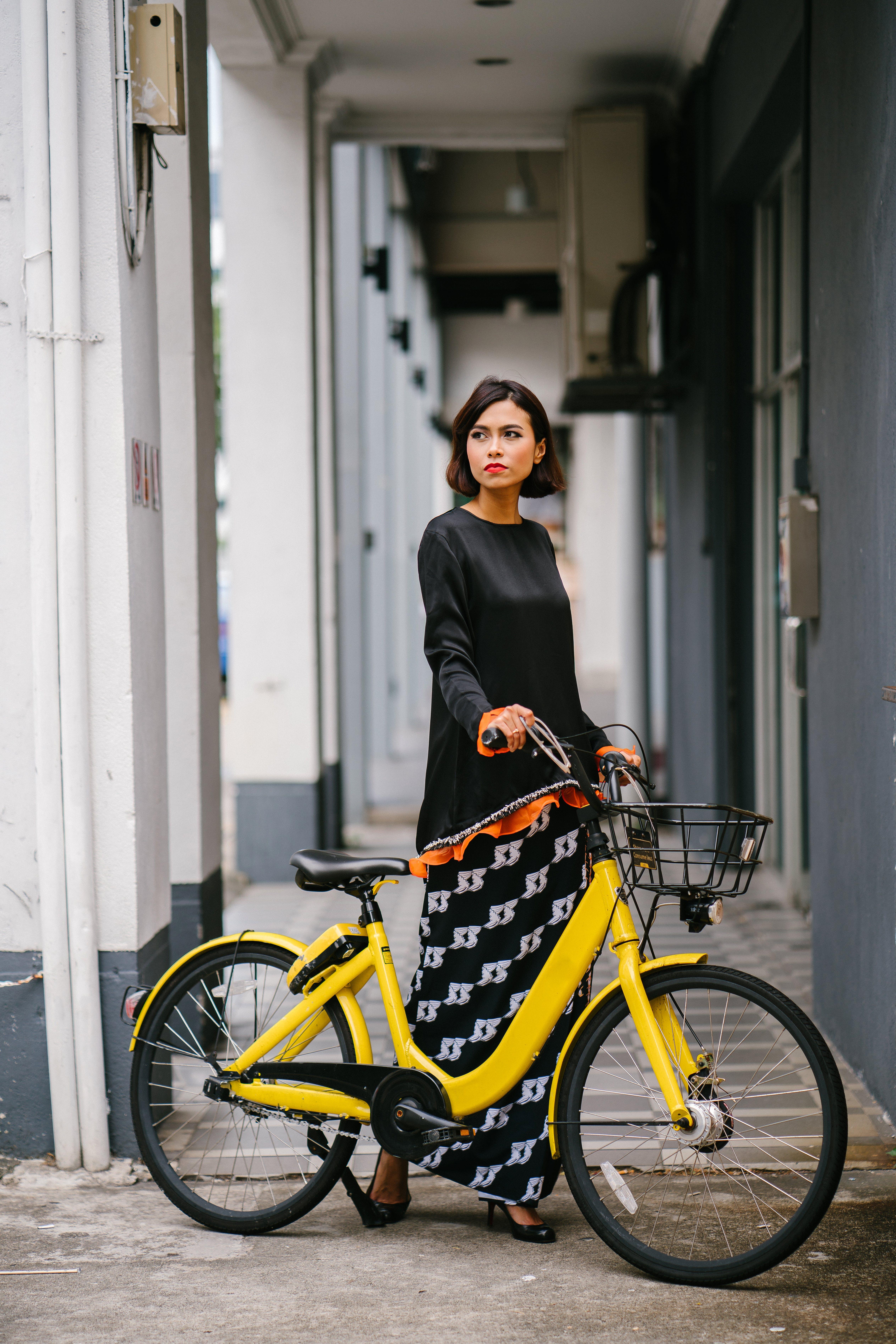 Woman Holding Yellow Bike at Daytime