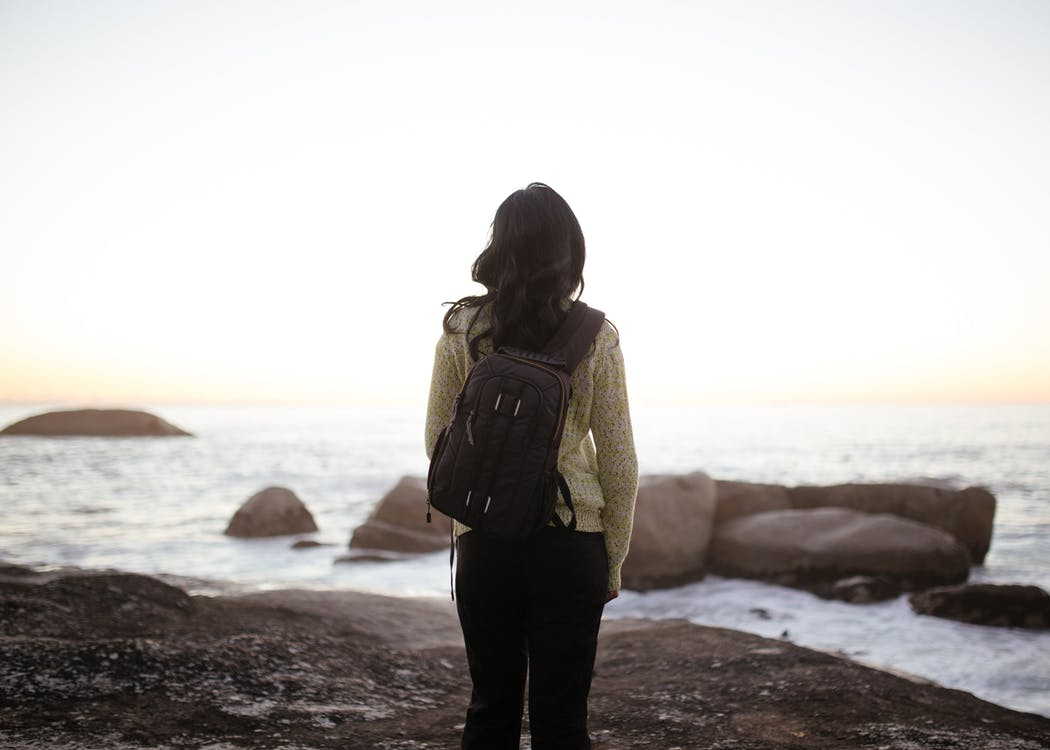 Woman Wearing White Long-sleeved Top and Black Pants Carrying Black Backpack While Standing on Shore during Adytime