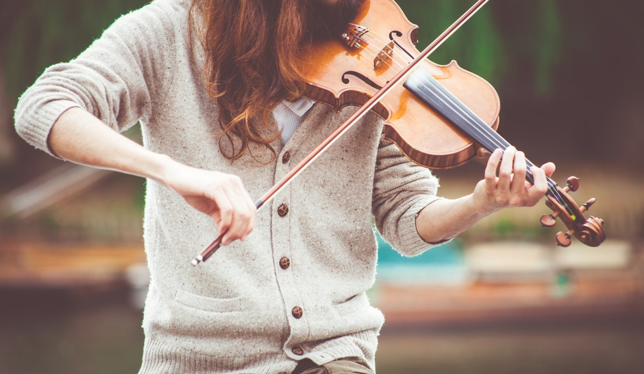 Woman in Gray Cardigan Playing a Violin during Daytime