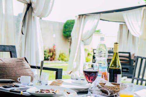 Стол с тарелкой еды, бутылкой вина и кружками