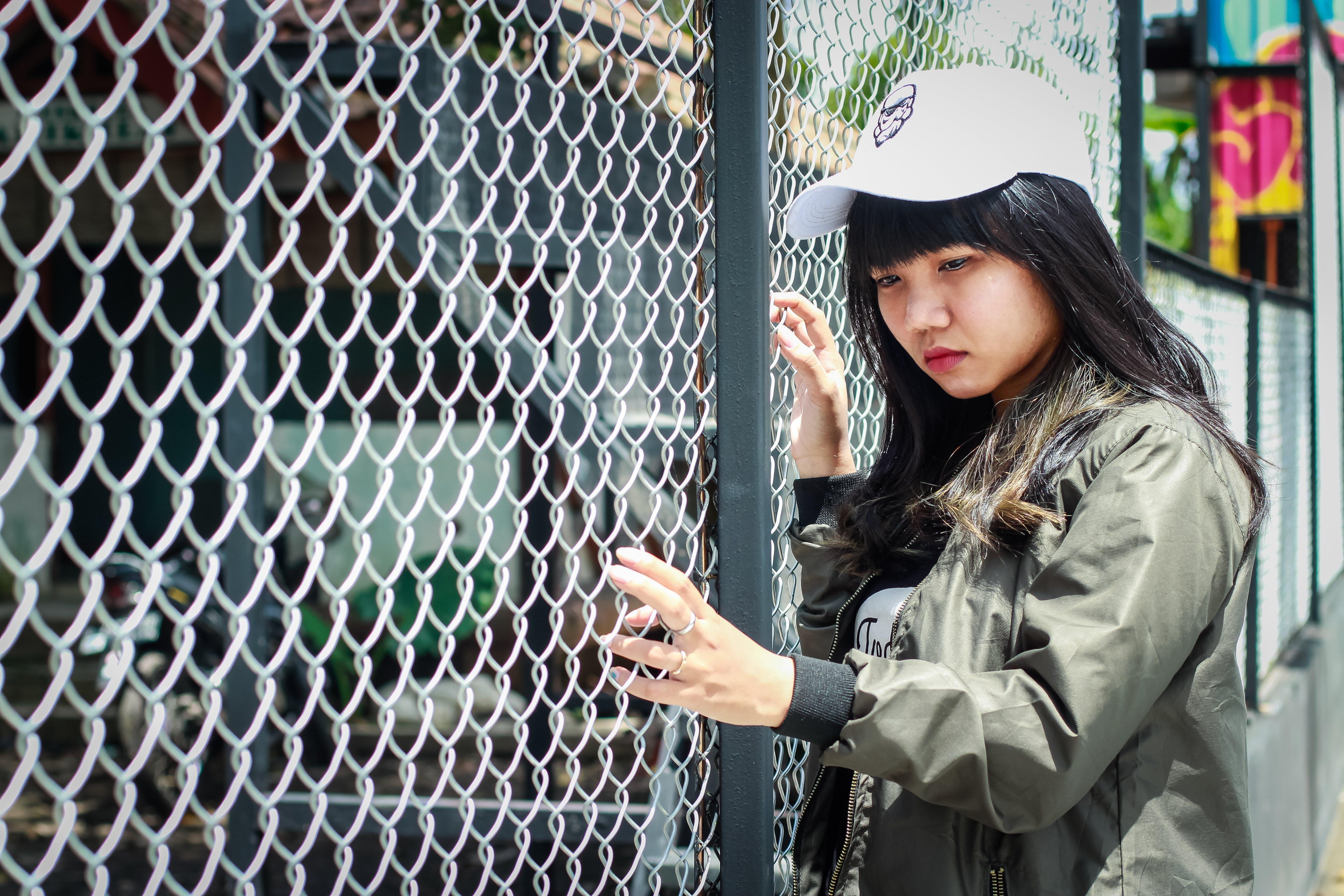 Woman Wearing Grey Bomber Jacket Leaning Near Grey Wire Fence