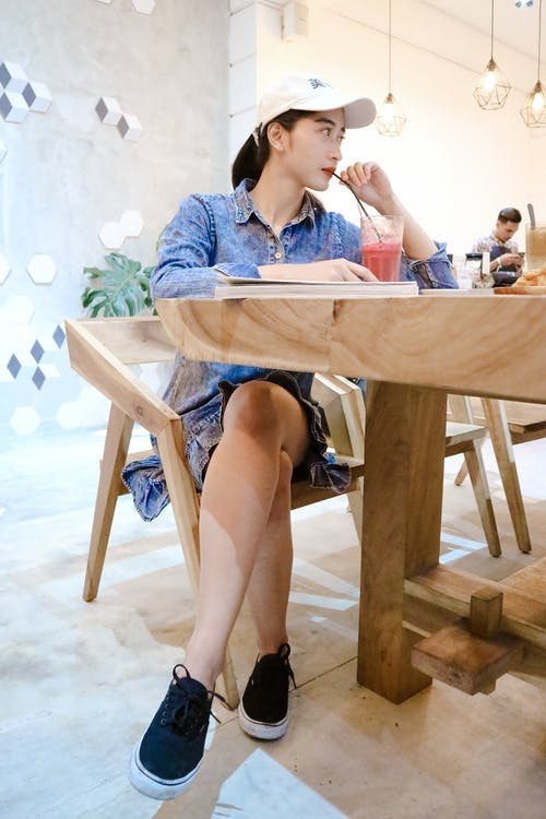 Woman Sits on Brown Wooden Chair Near Brown Table Inside Room