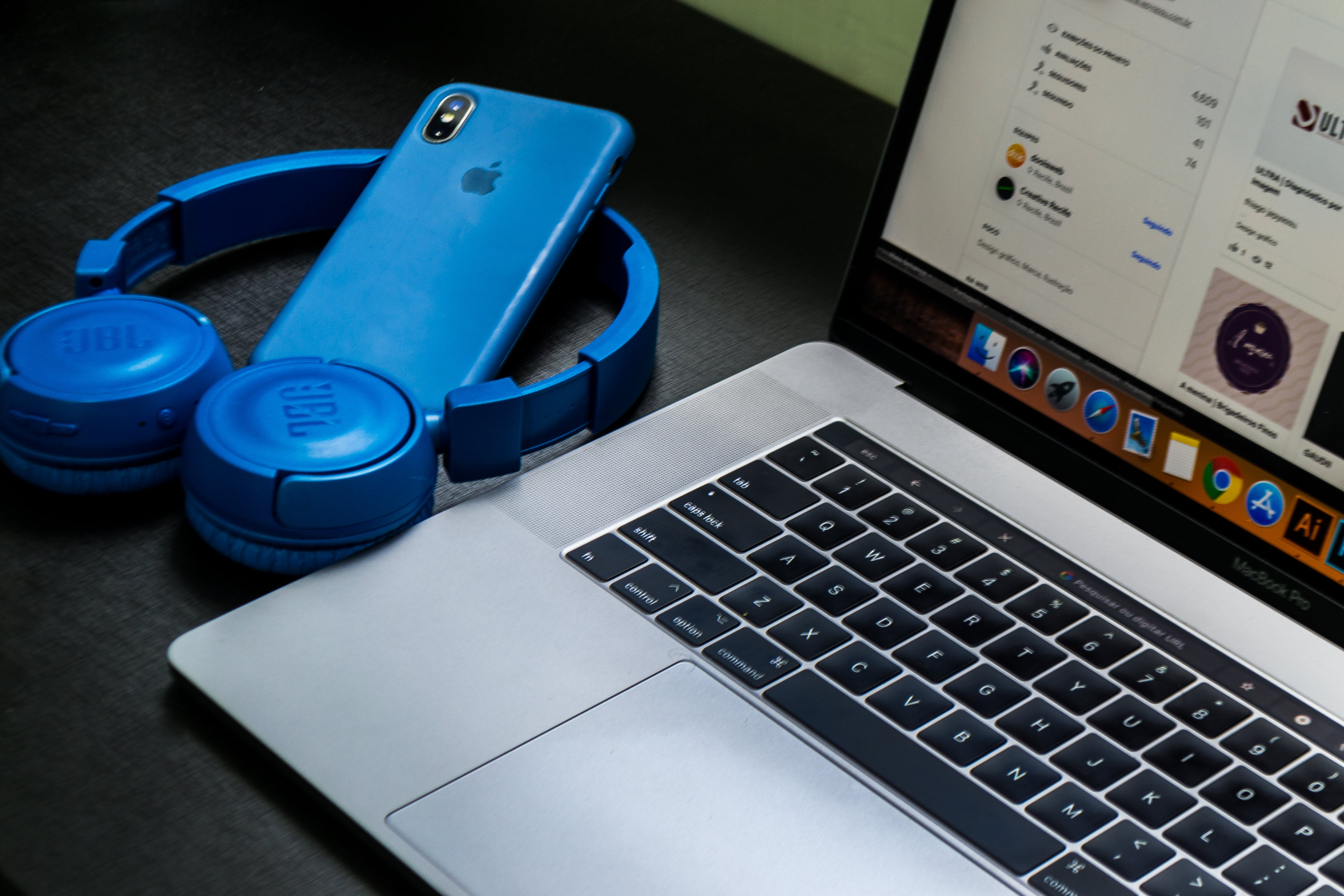 Macbook Pro Beside Blue Wireless Headphones