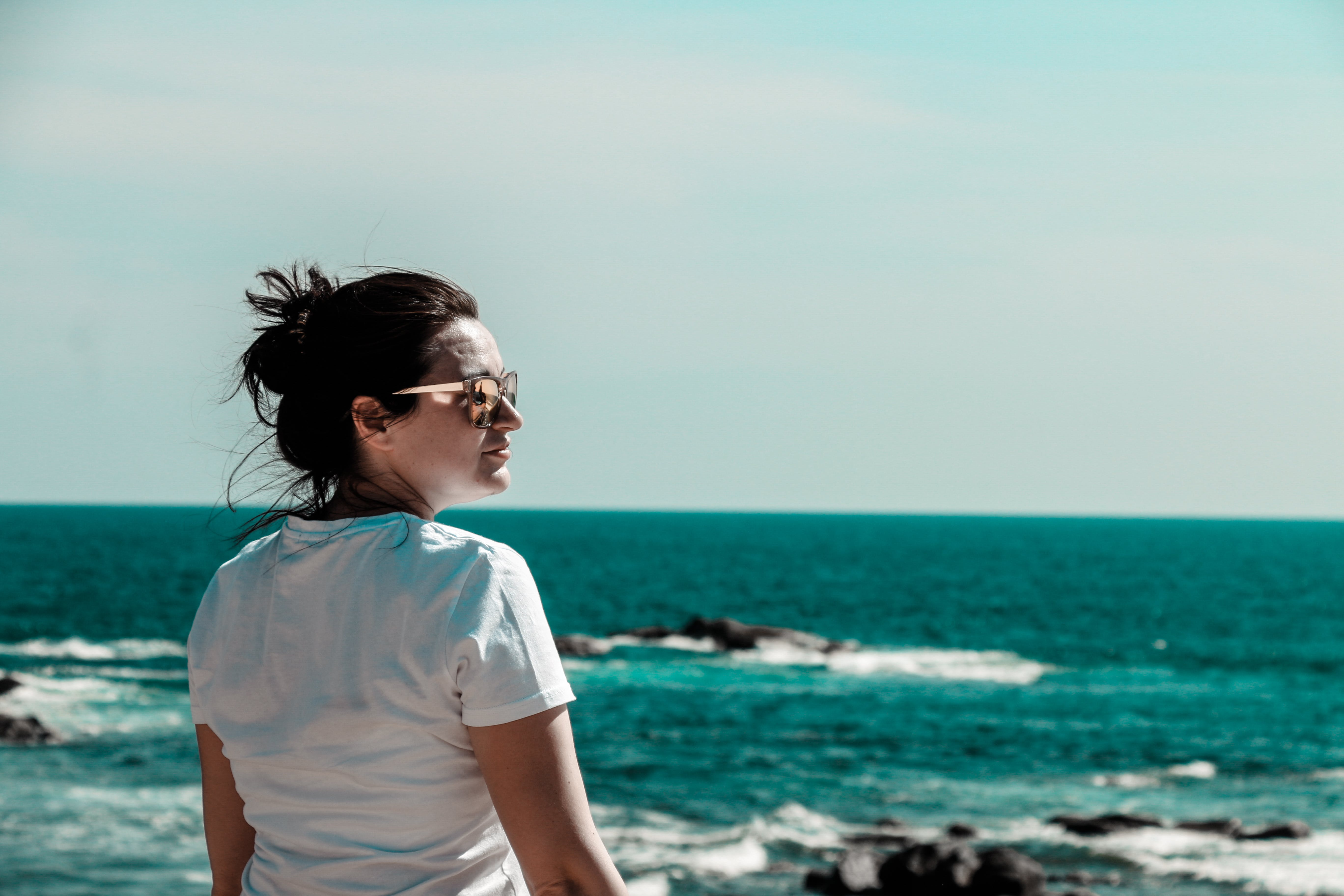 Woman Wearing White T-shirt With Distance at Sea With Rock Formations