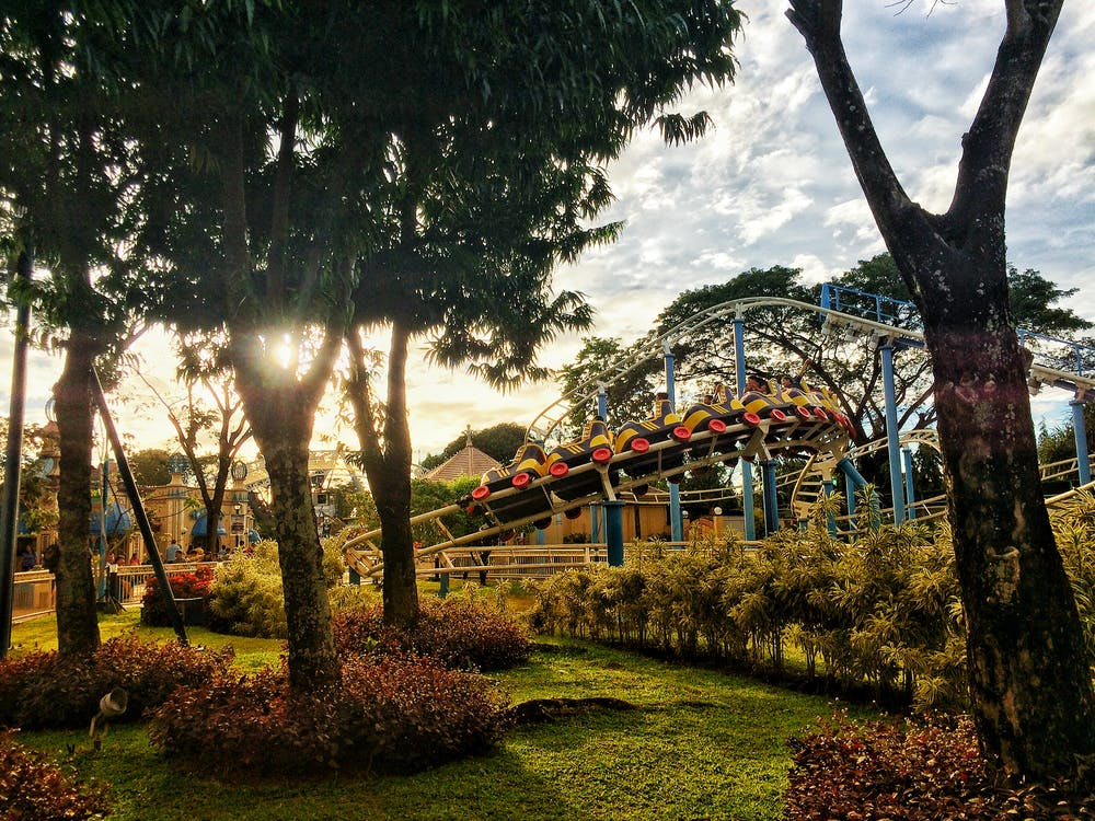 Roller Coaster Ride Near Trees Under Blue Clouds