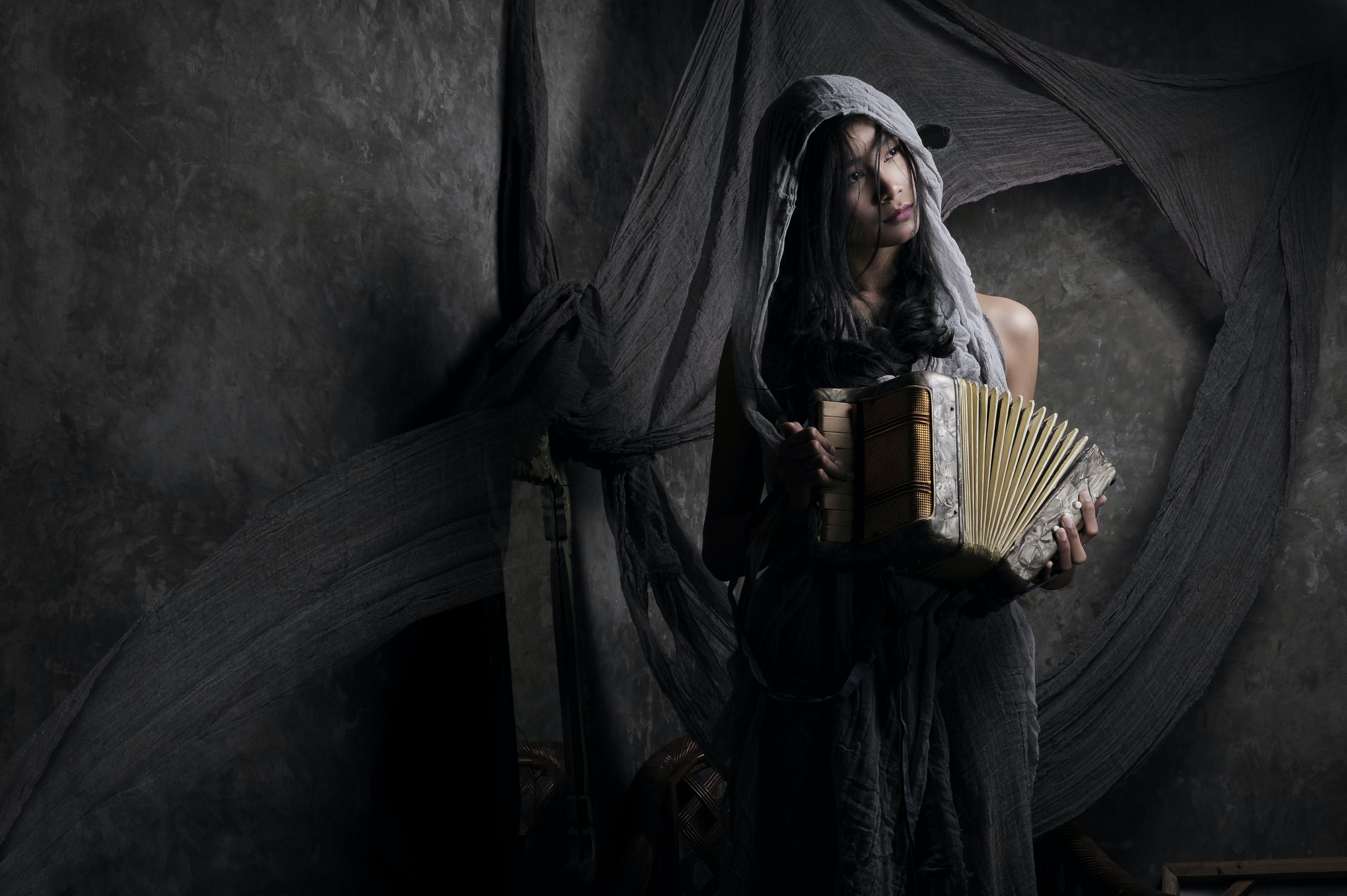 Woman Wearing Gray Scarf Holding Accordion